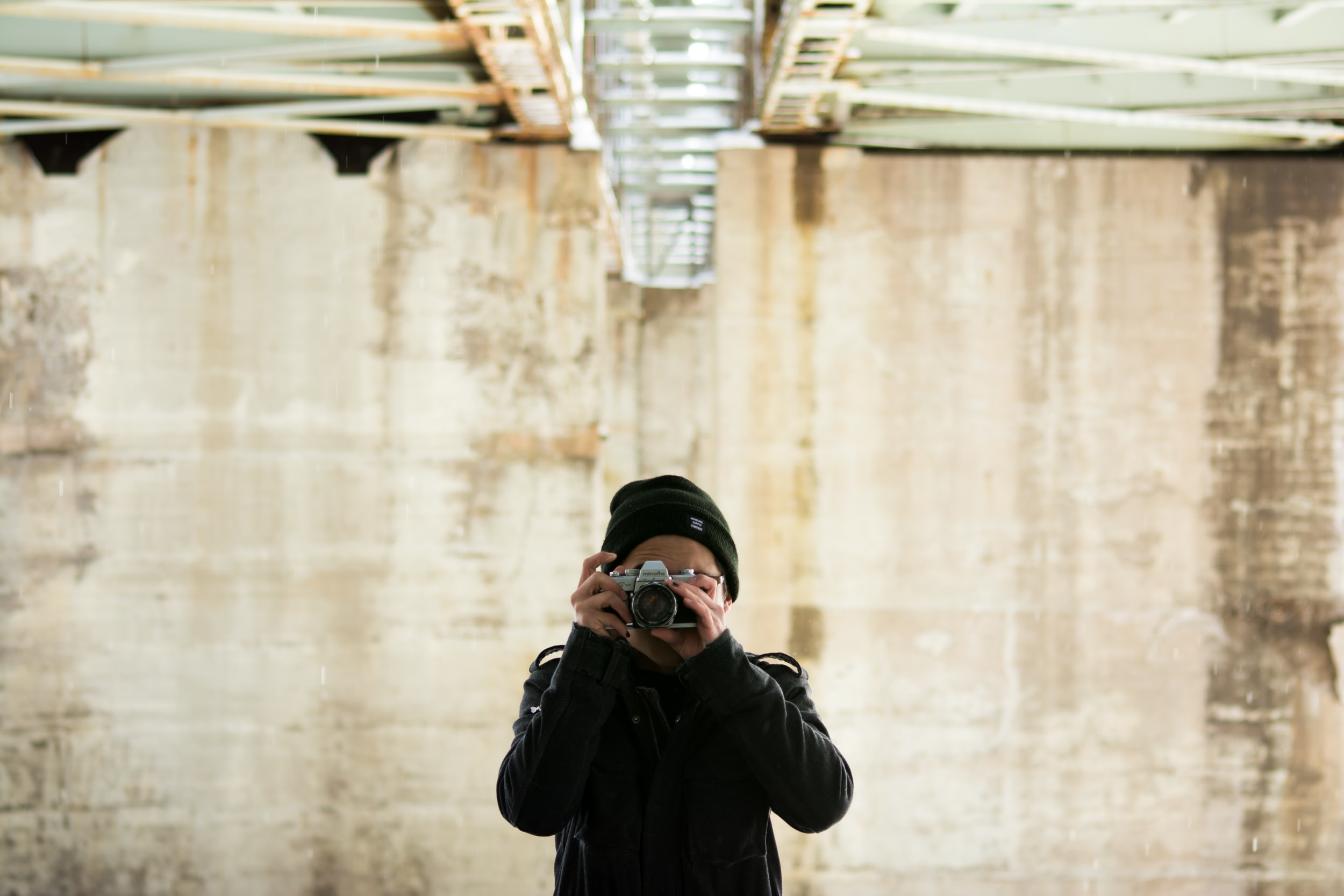 A photographer in a black knit cap points his camera at the person taking the picture