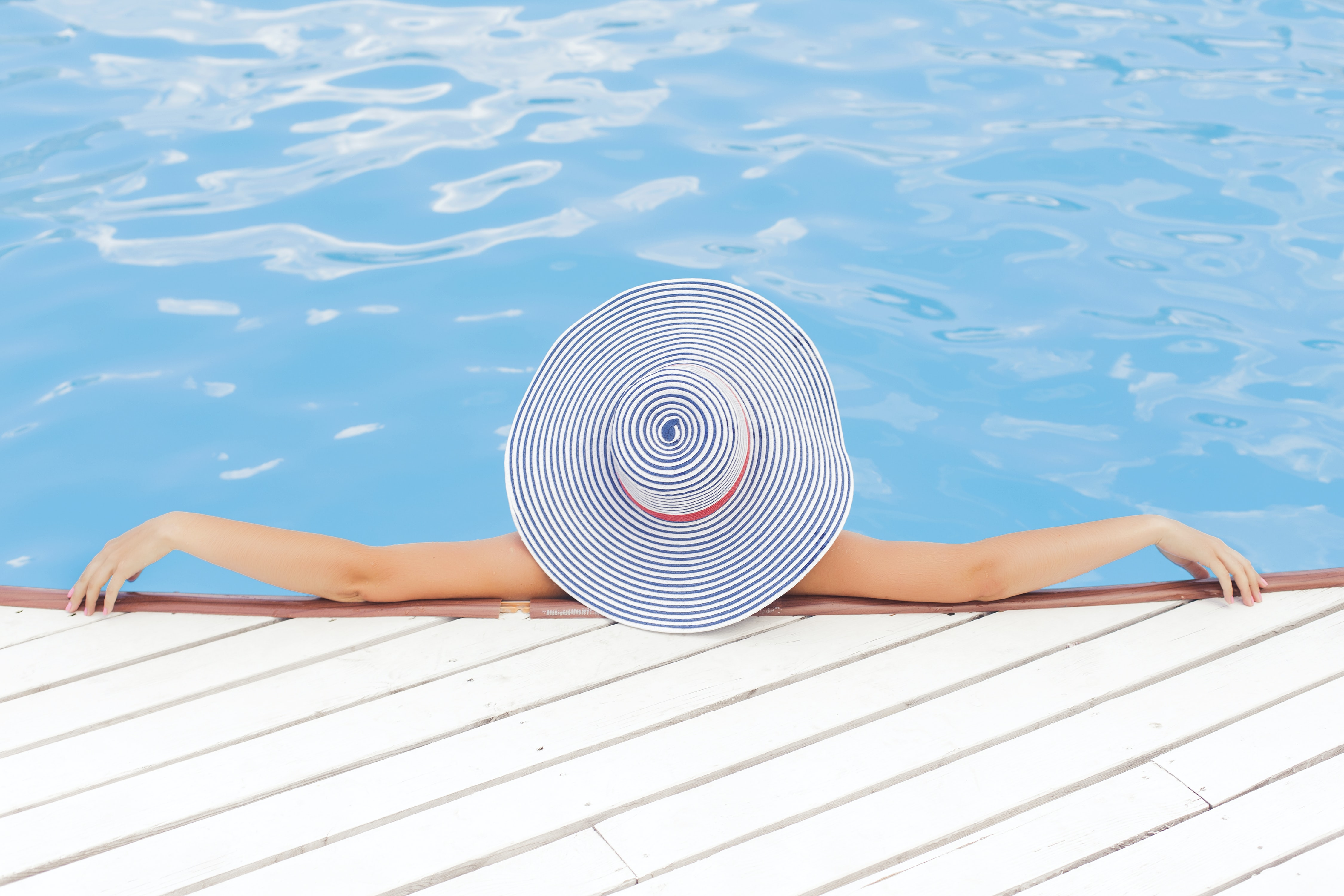 woman leaning on white concrete surface beside swimming pool during daytime