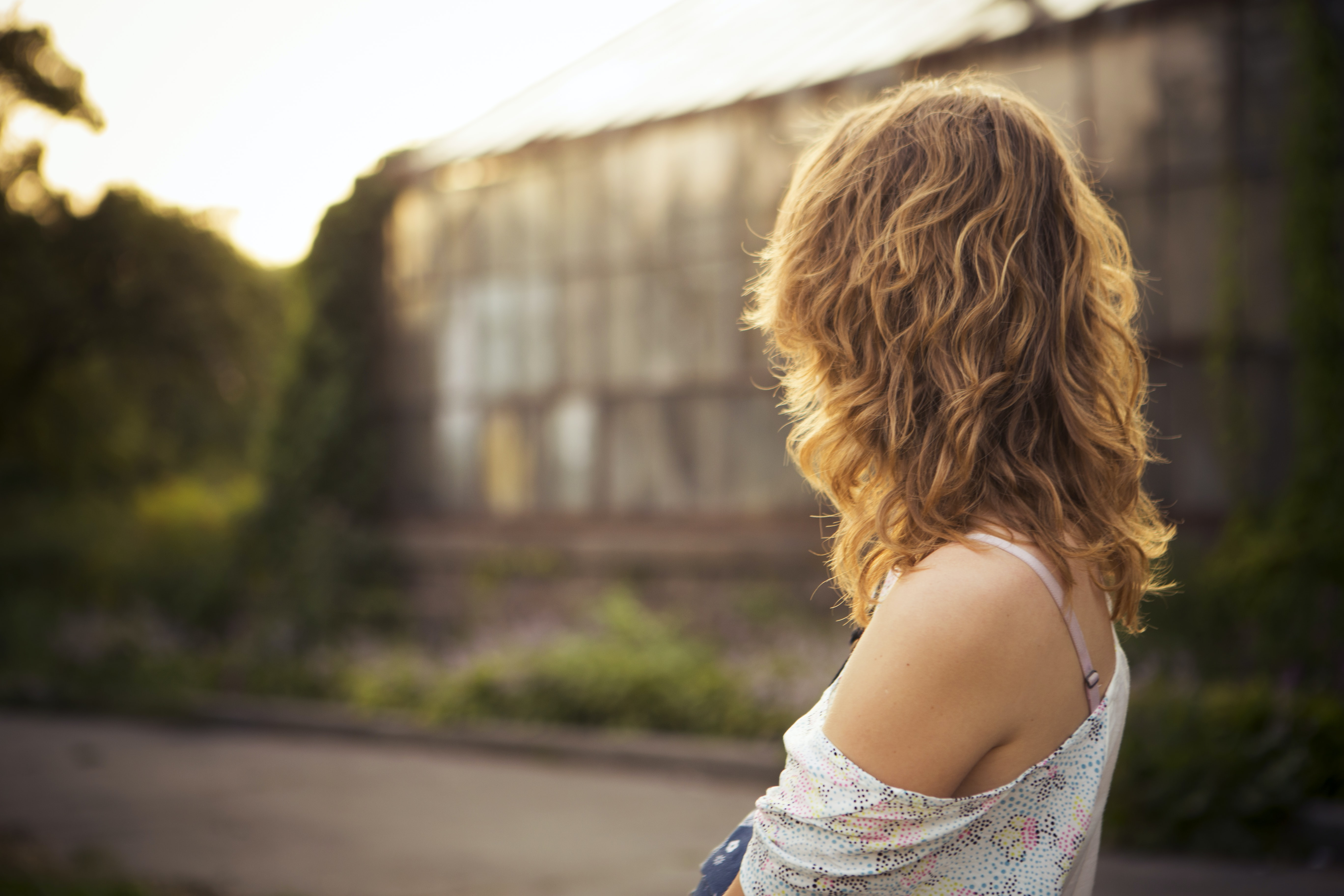 A woman with wavy hair and off-the-shoulder top looks away toward a greenhouse
