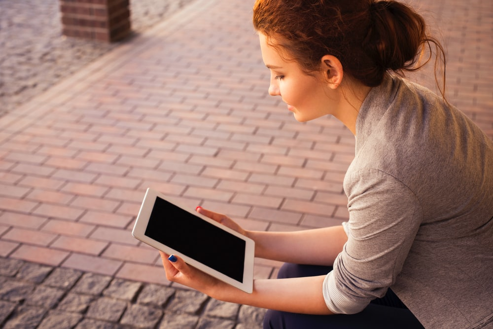 A woman with a blue painted nails holding and reading on an ipad tablet beside a walkway