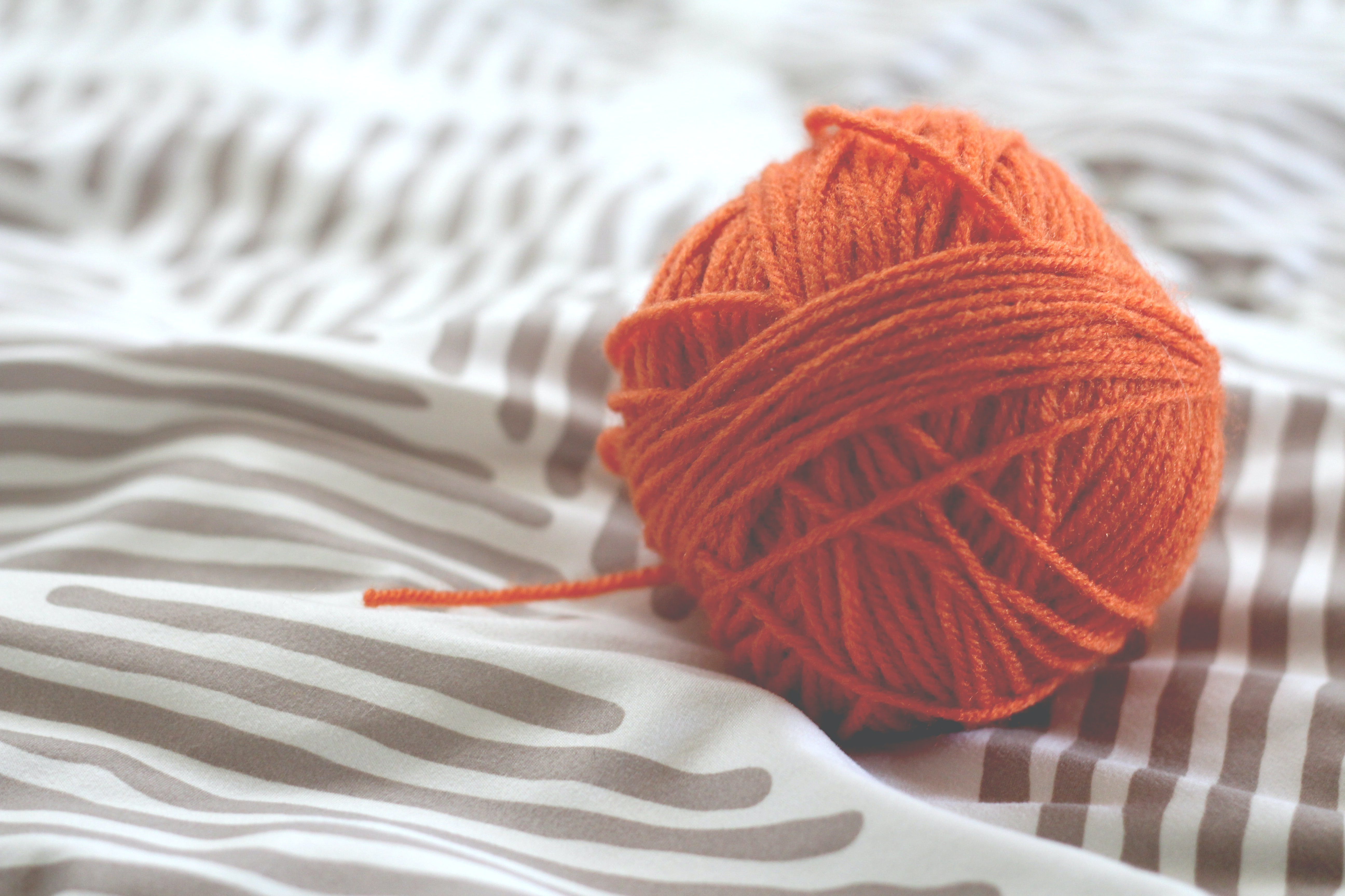 A red ball of yarn on a blanket