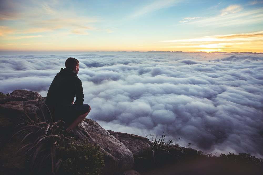 man sitting on gray rock while staring at white clouds
