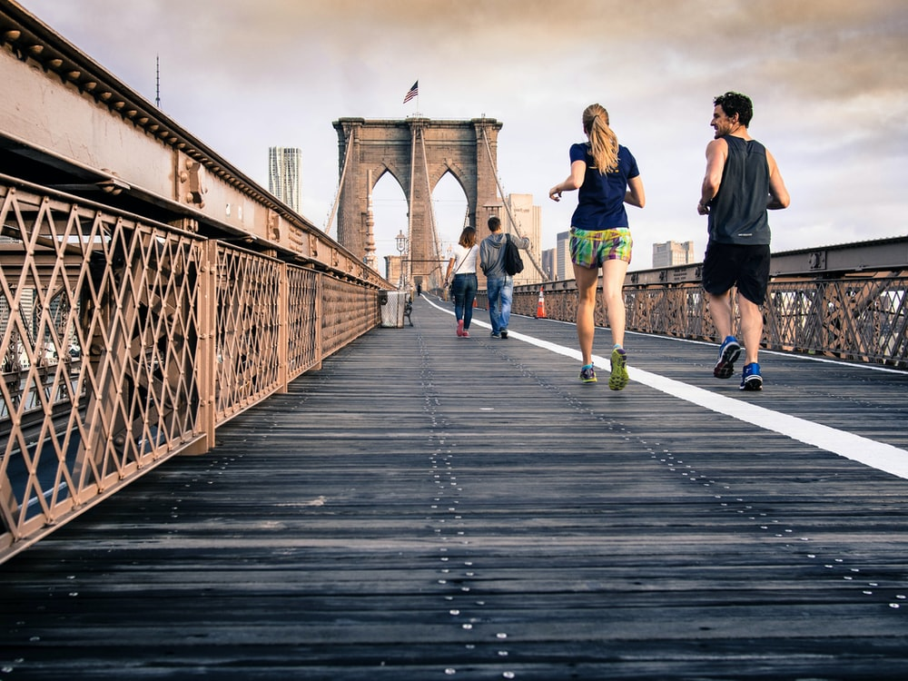 man and woman in black tops jogging at bridge under clear skies