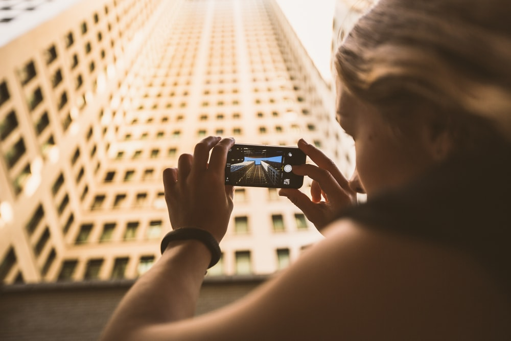selective focus photography of woman taking low angle photo of high-rise building