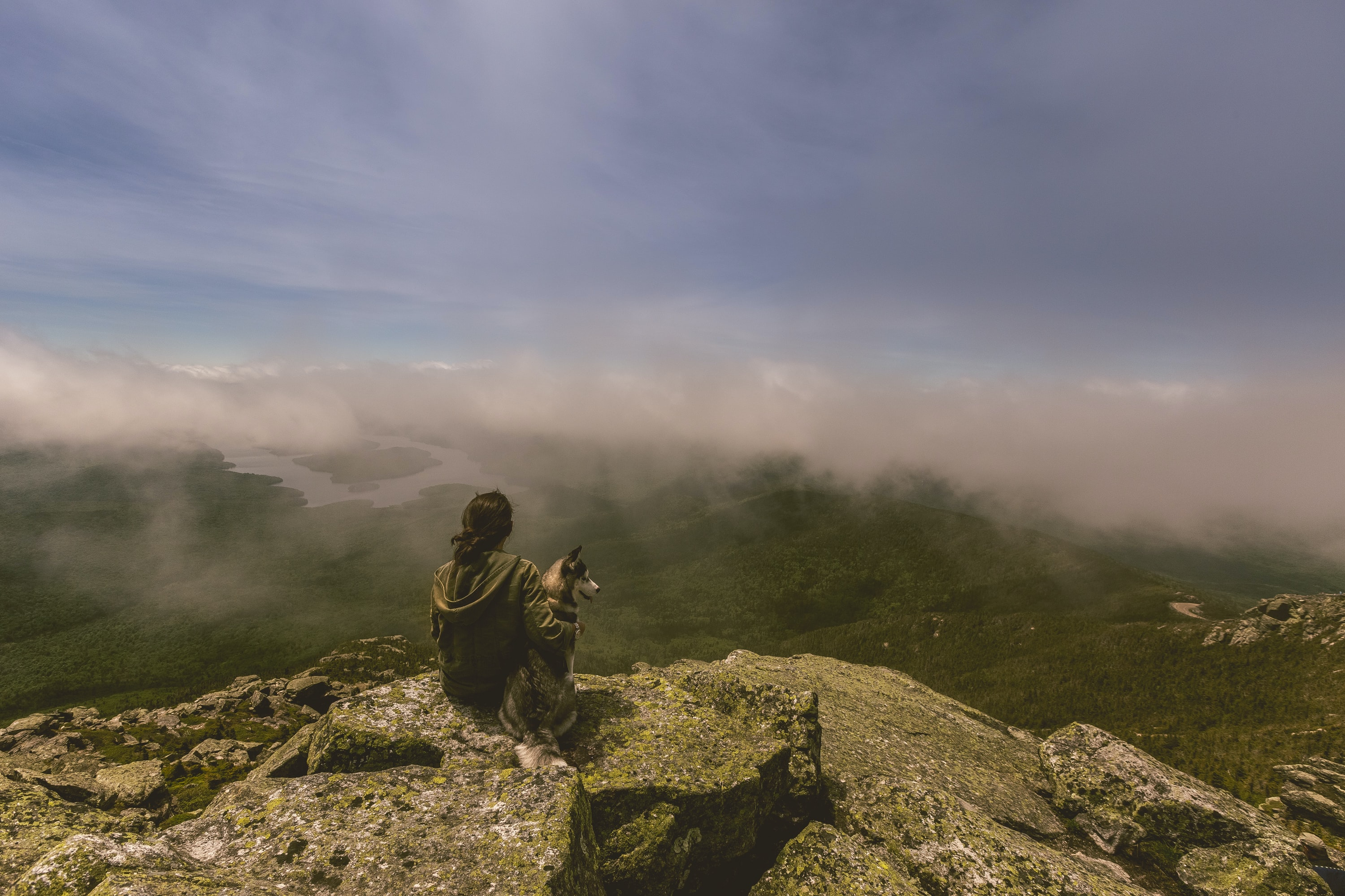 woman and dog sitting on gray concrete rock formation in front of mountain with fogs