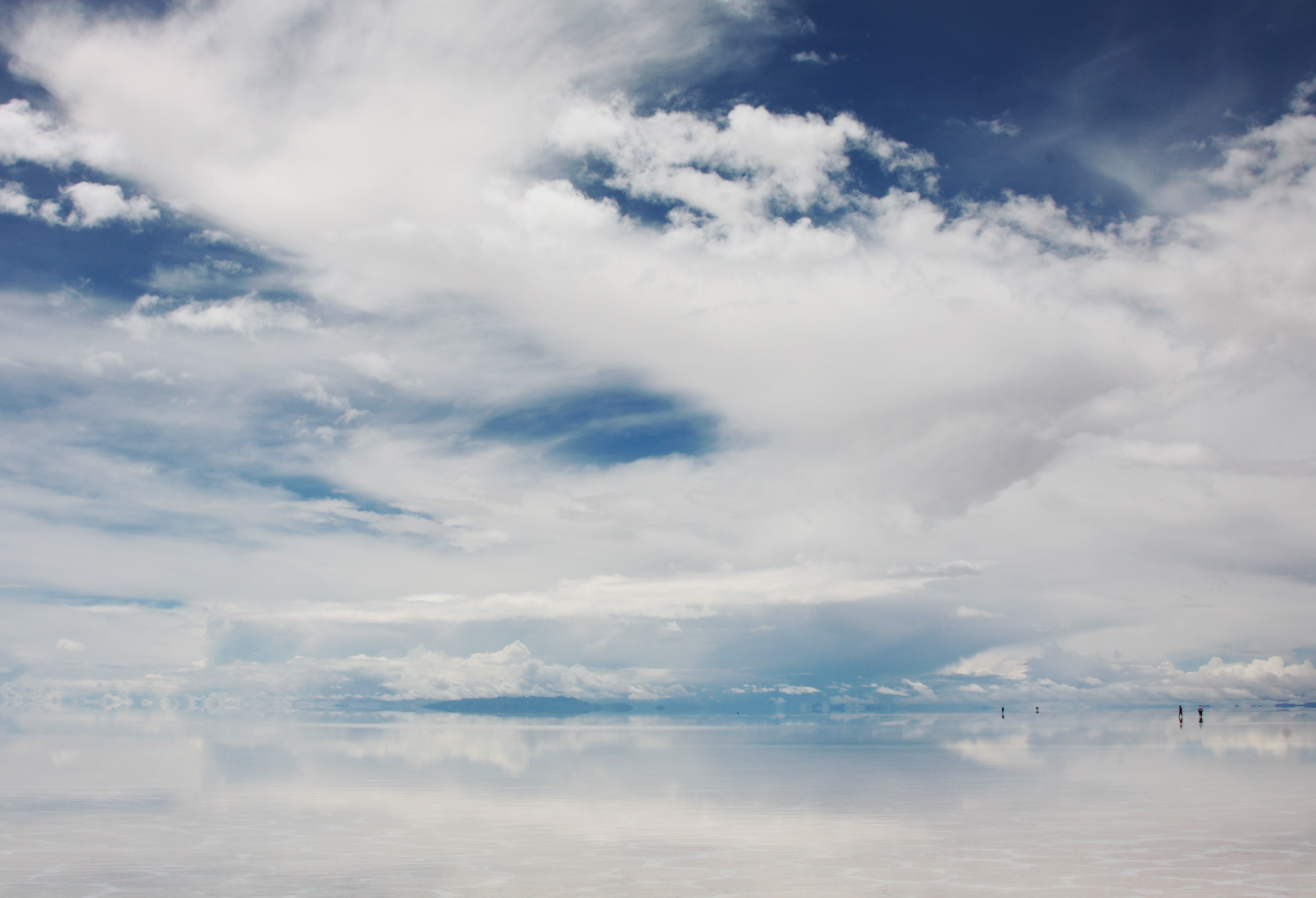 Heavy white clouds over reflective water with human silhouettes looming on the horizon