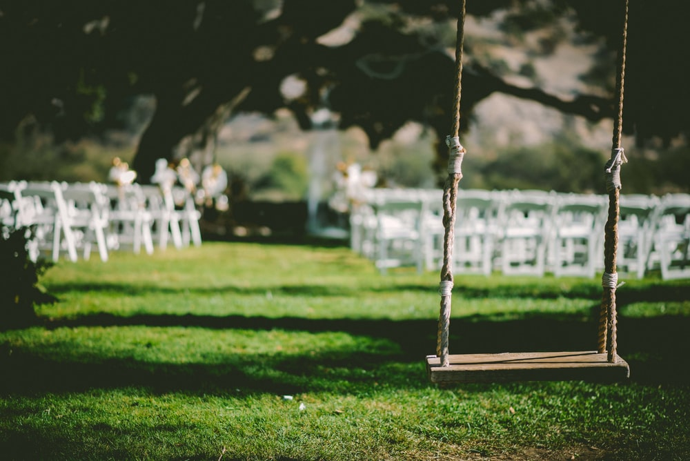 closeup photo of brown wooden swing during daytime
