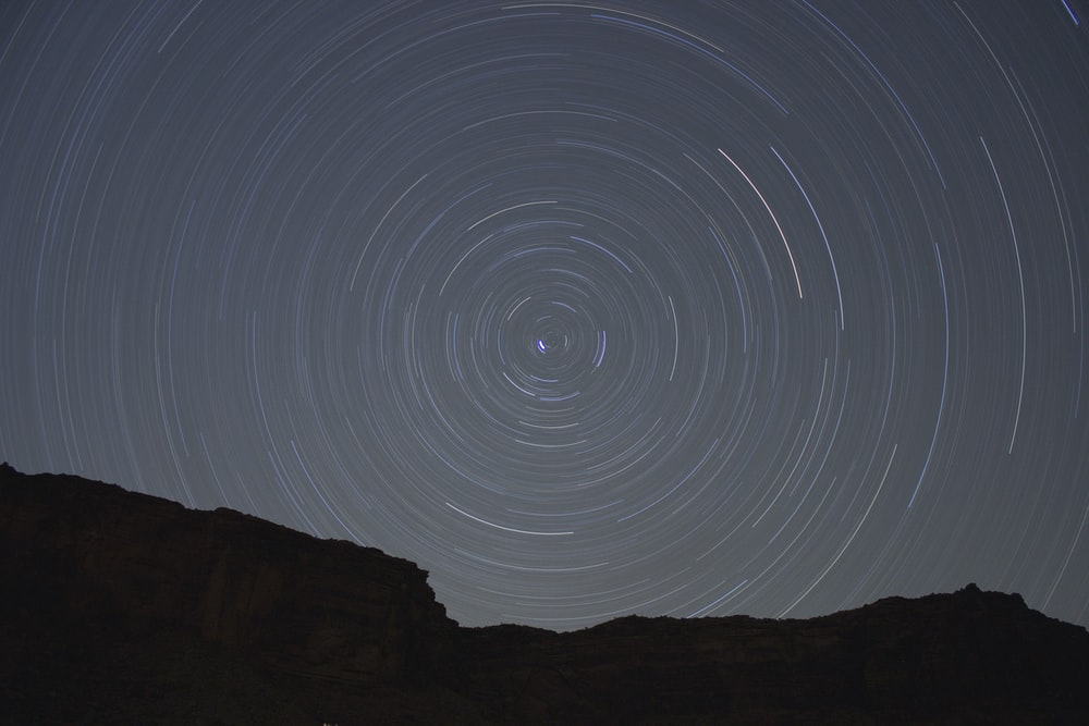 Concentric circles created by stars moving through the night sky over a silhouetted rock face