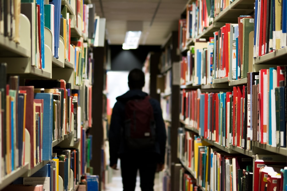 man with backpack beside a books