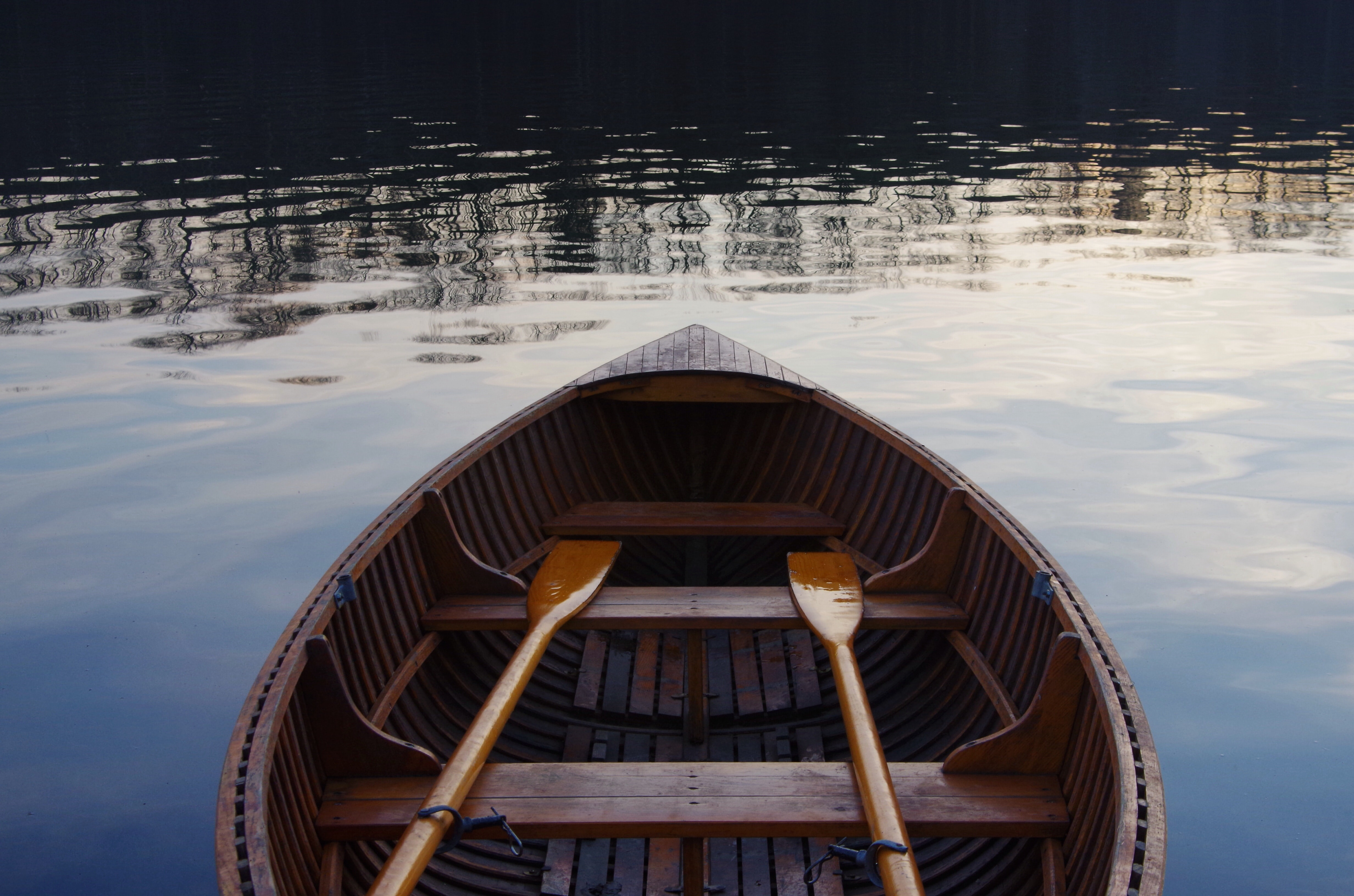 The inside of a small wooden boat on water with two oars