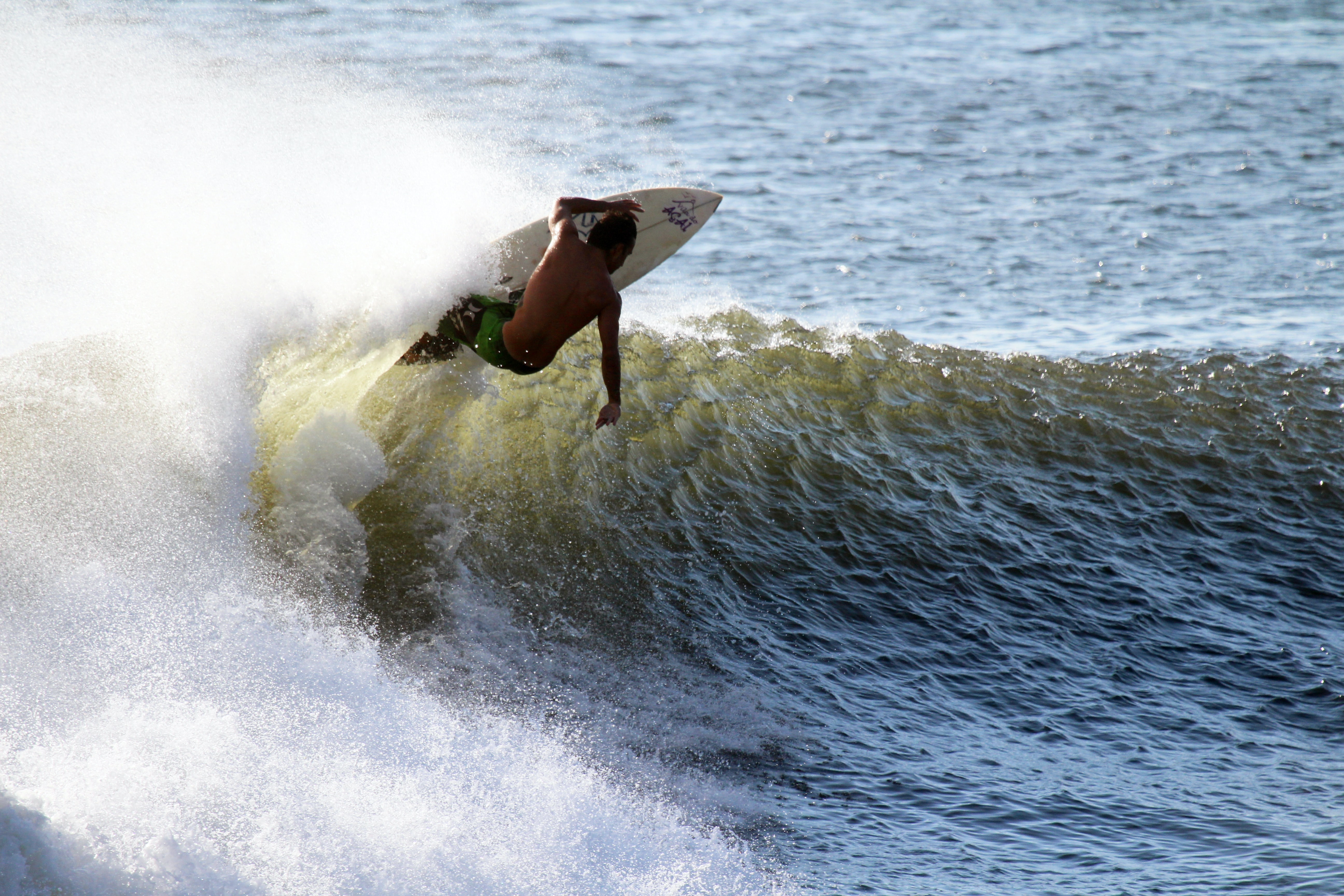 A surfer riding a white board, performing a trick on a rolling wave in the sea