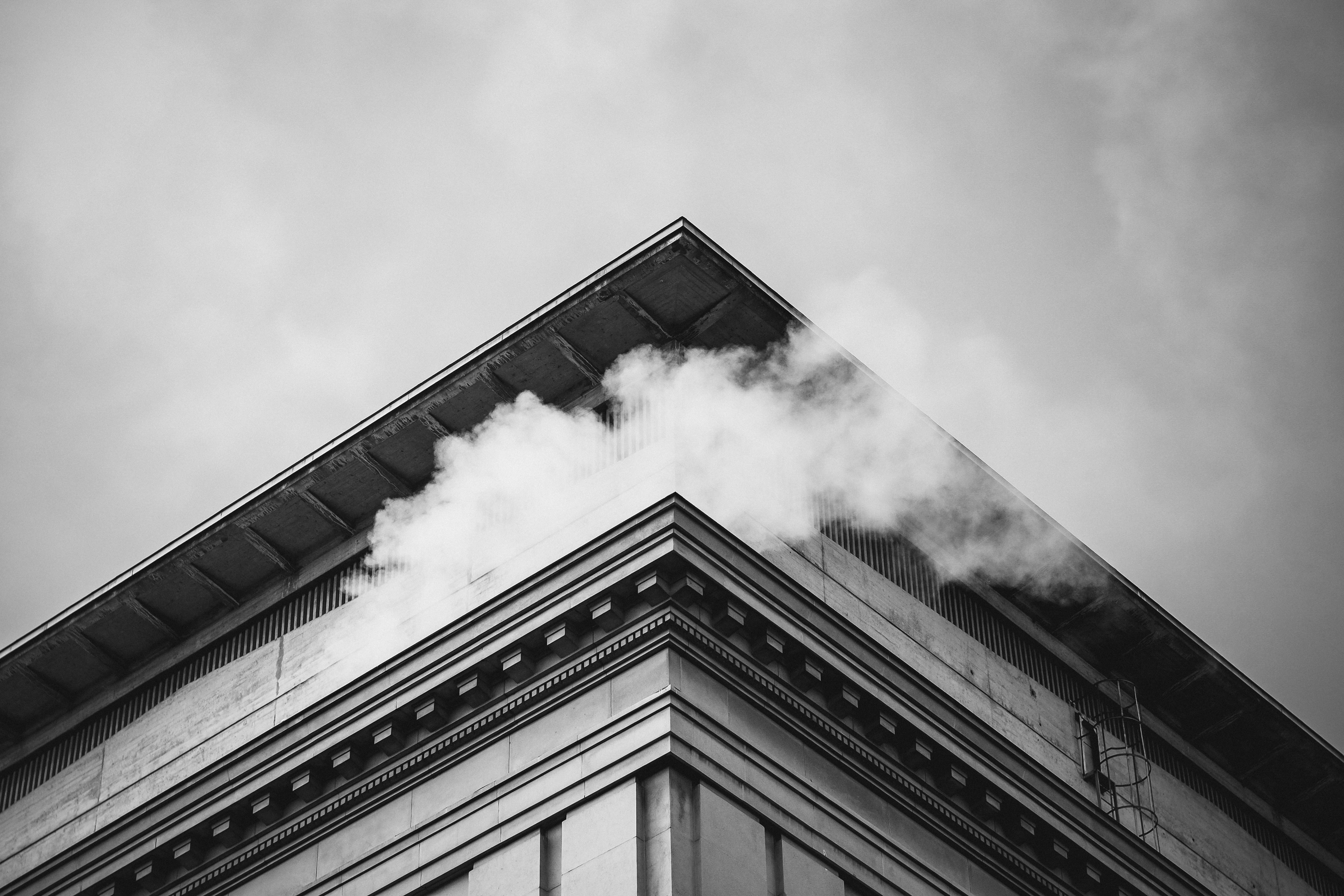 grayscale photo of smoke on top of building