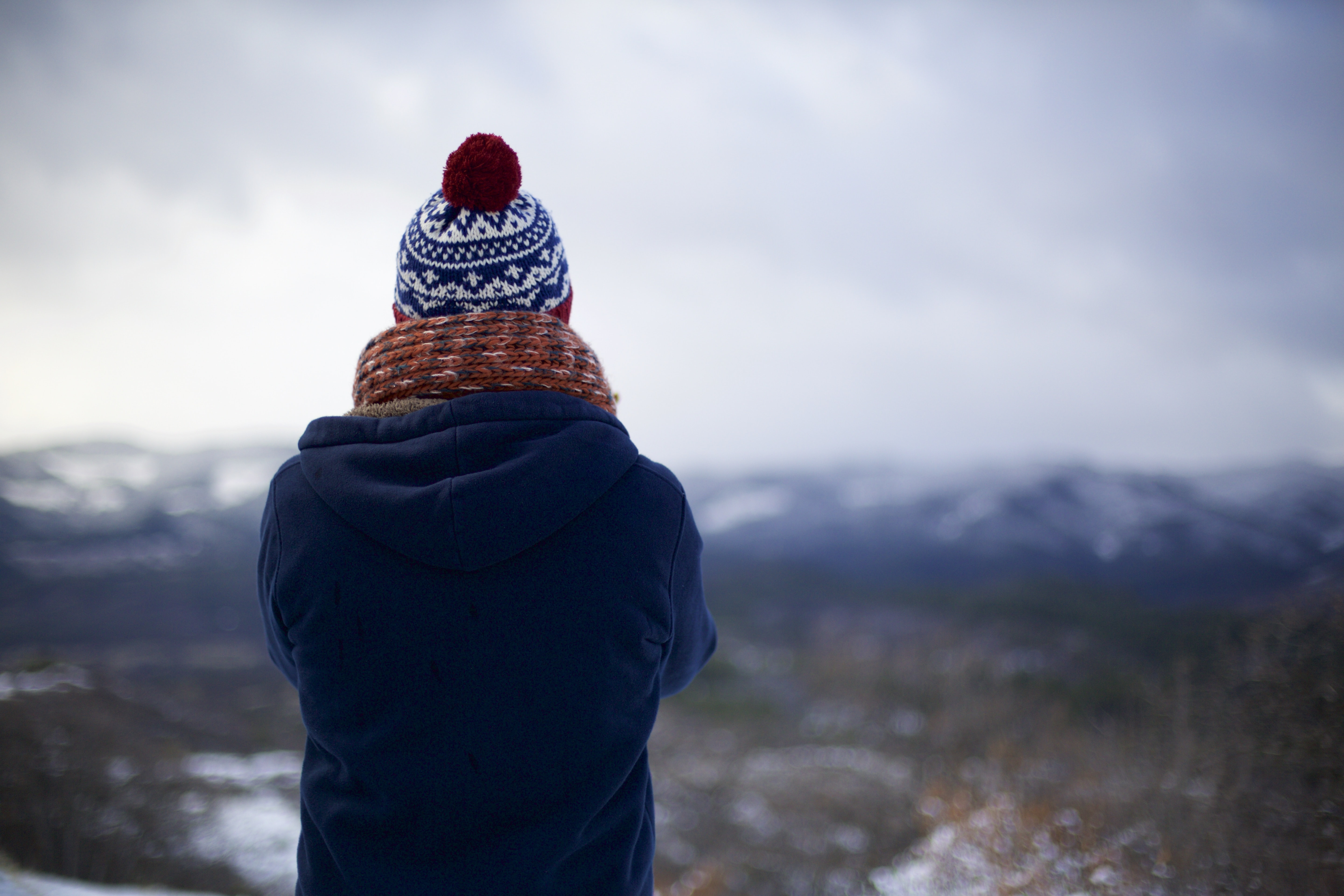 The back of a person  with crossed arms wearing a knit cap, scarf, and blue coat is visible as he or she stares out into snowy wilderness