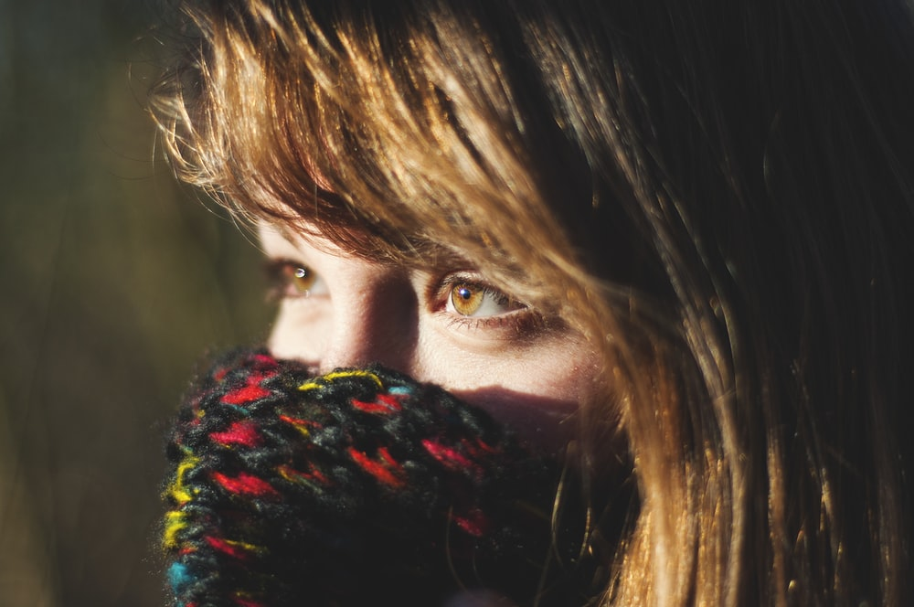 woman covering her multicolored knit mask