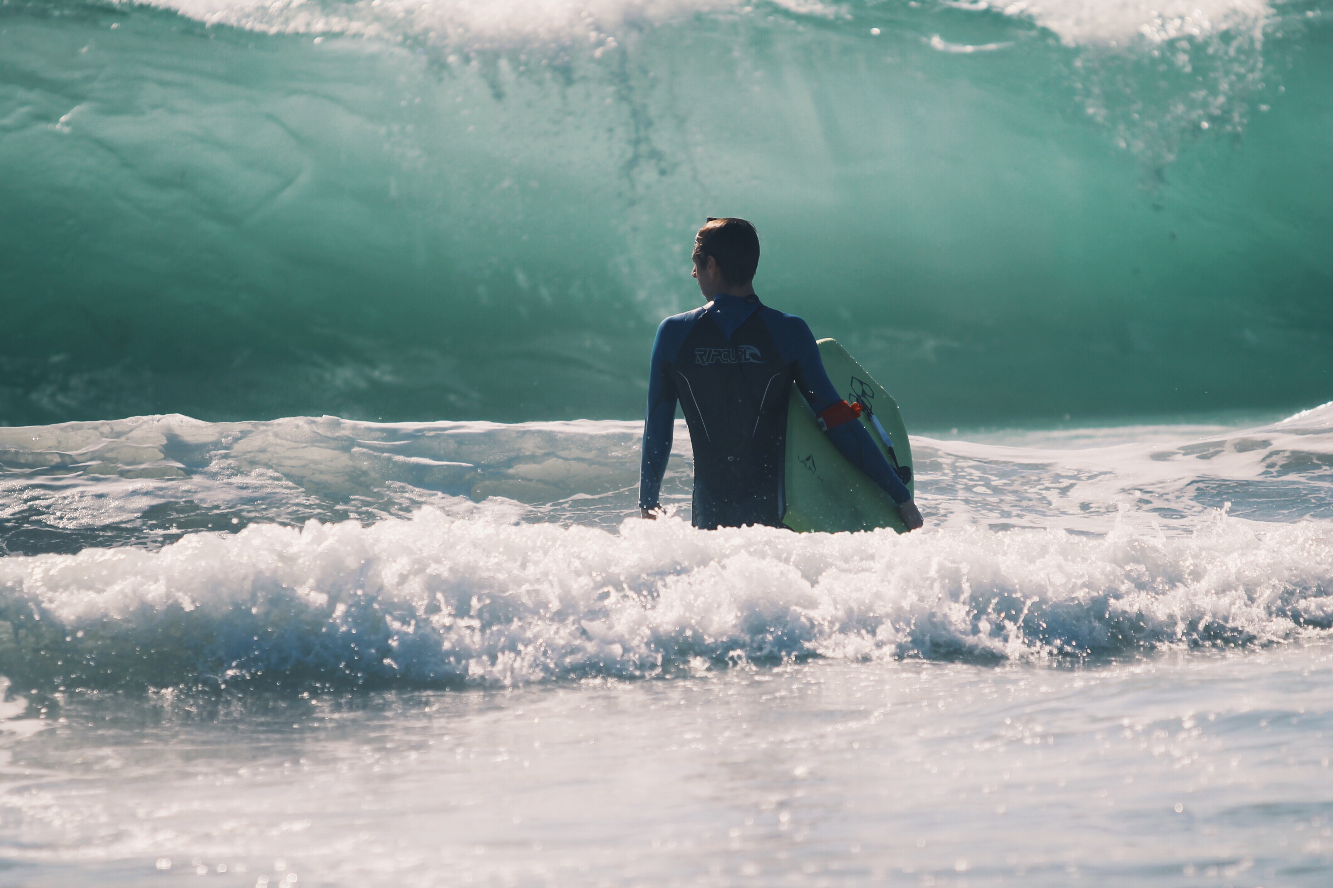 A man in a wetsuit stood in the sea, holding his board, looking out at a massive onrushing wave