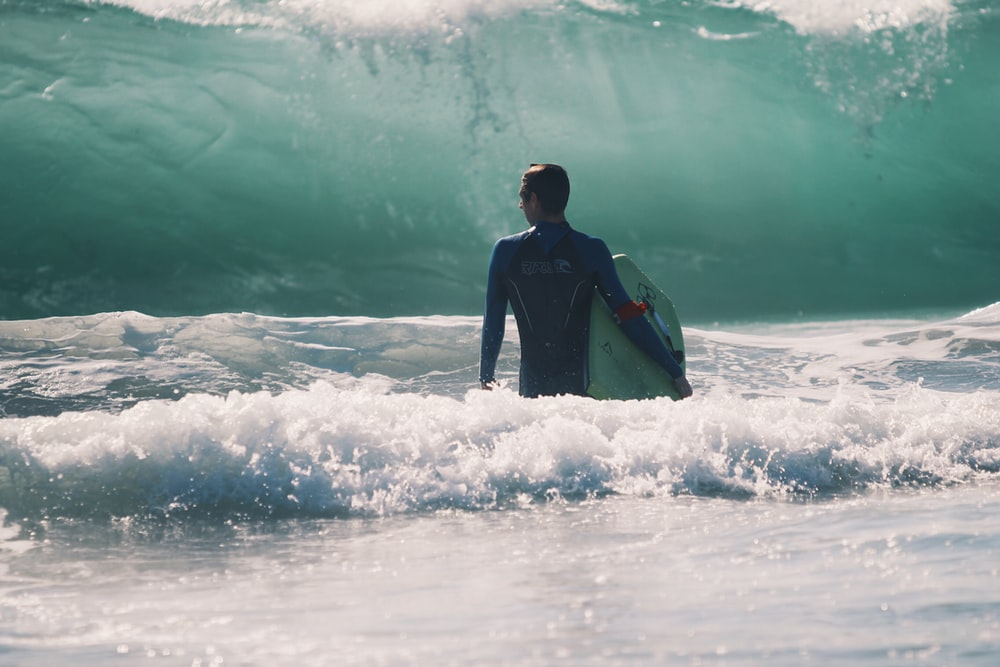 man standing in body of water holding surfboard