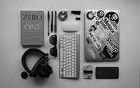 black corded headphones, silver MacBook, Apple wireless keyboard, and Apple Magic Mouse