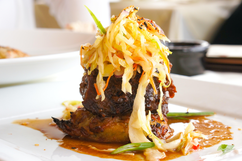 Gourmet steak dinner topped with shredded vegetables