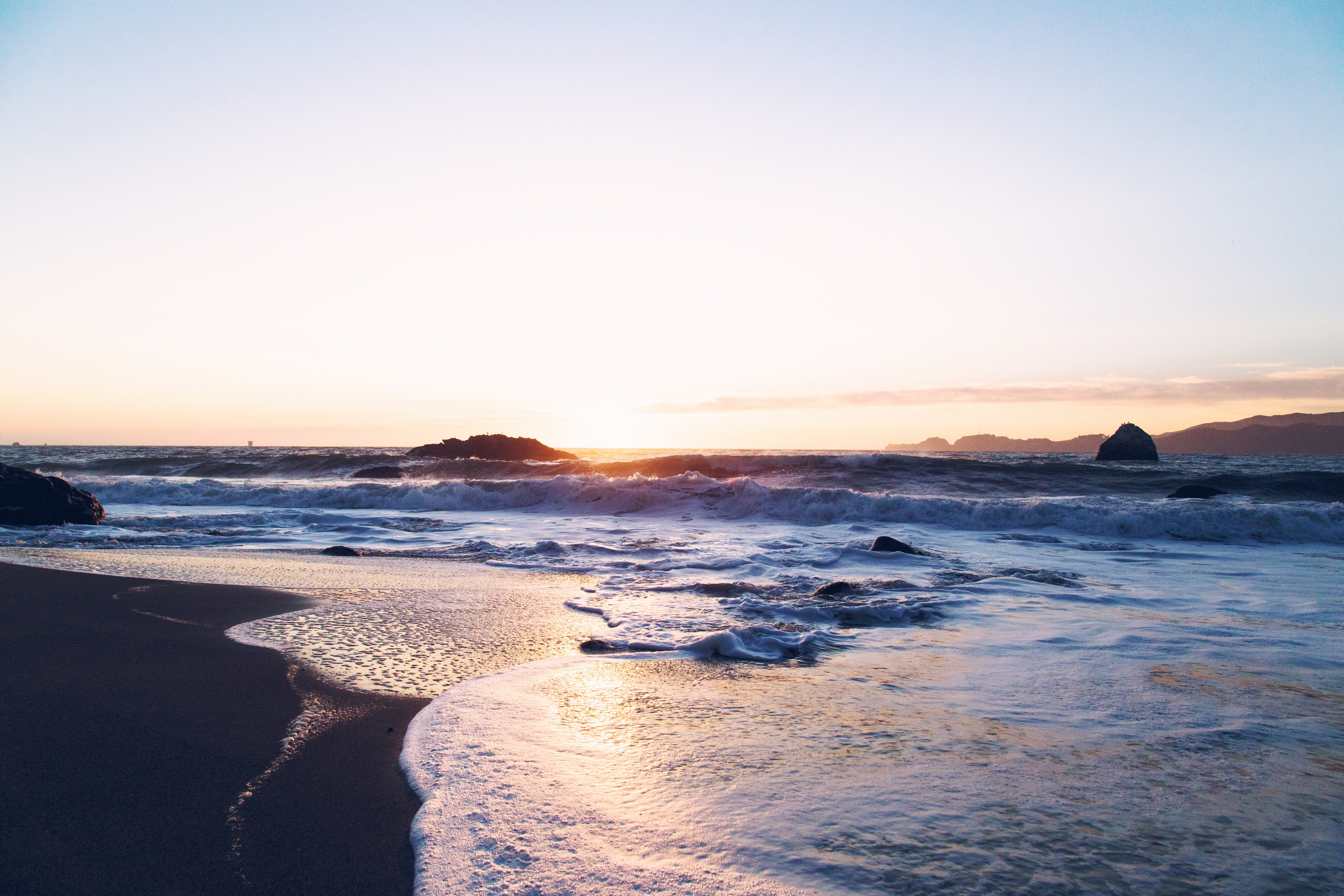Landscape view of lonely beach with the busy ocean at sunrise