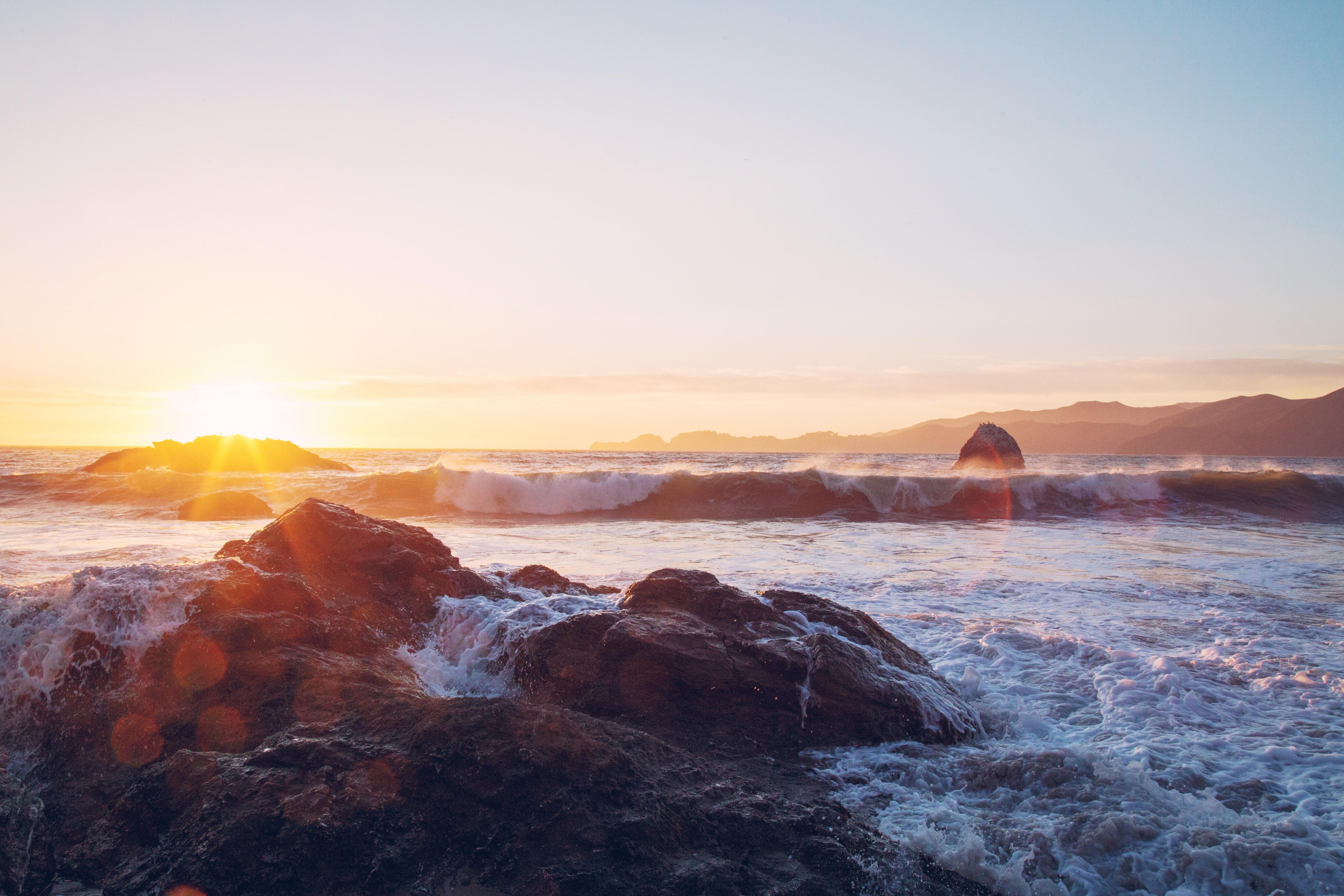 White sea waves hitting against rocks near the shore during sunset