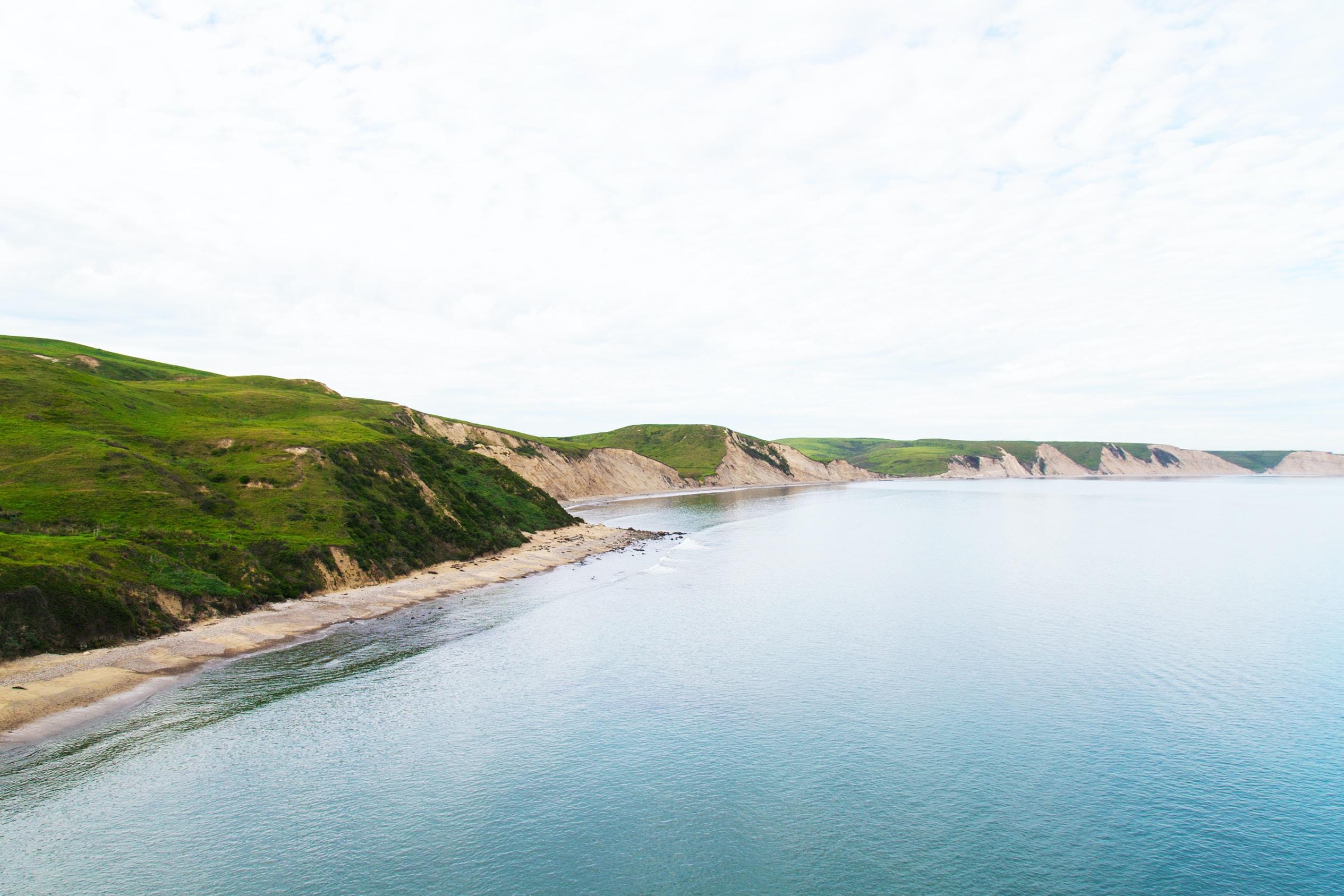 A sandy coastline with low grassy cliffs