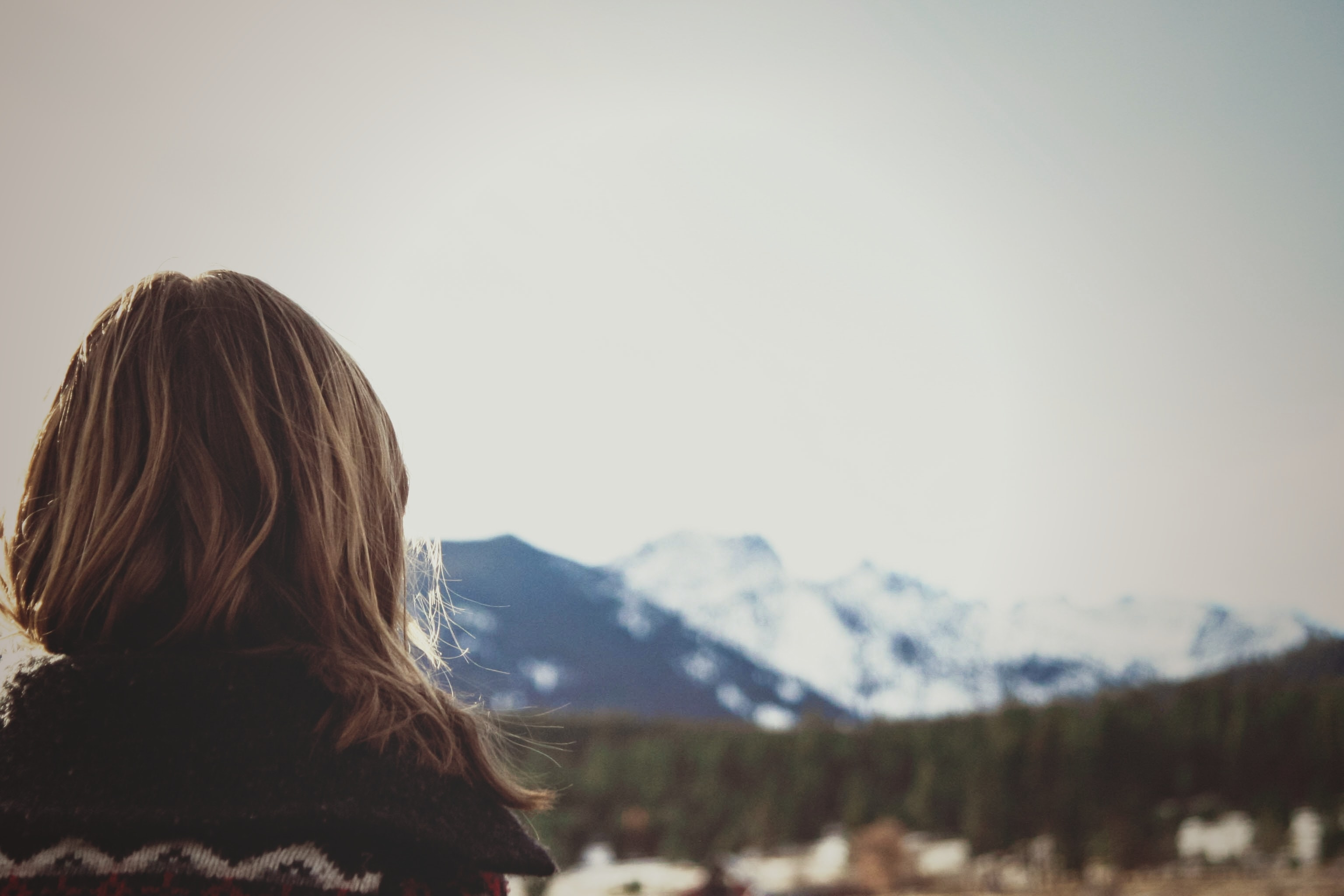 A blonde woman in a sweater looking at the distant snow-capped mountains