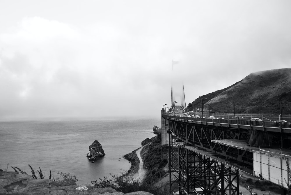 gray scale photo of bridge near body of water