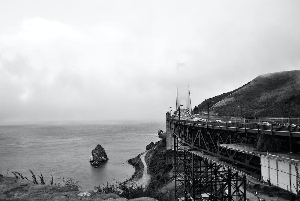 gray scale photo of bridge near body of water