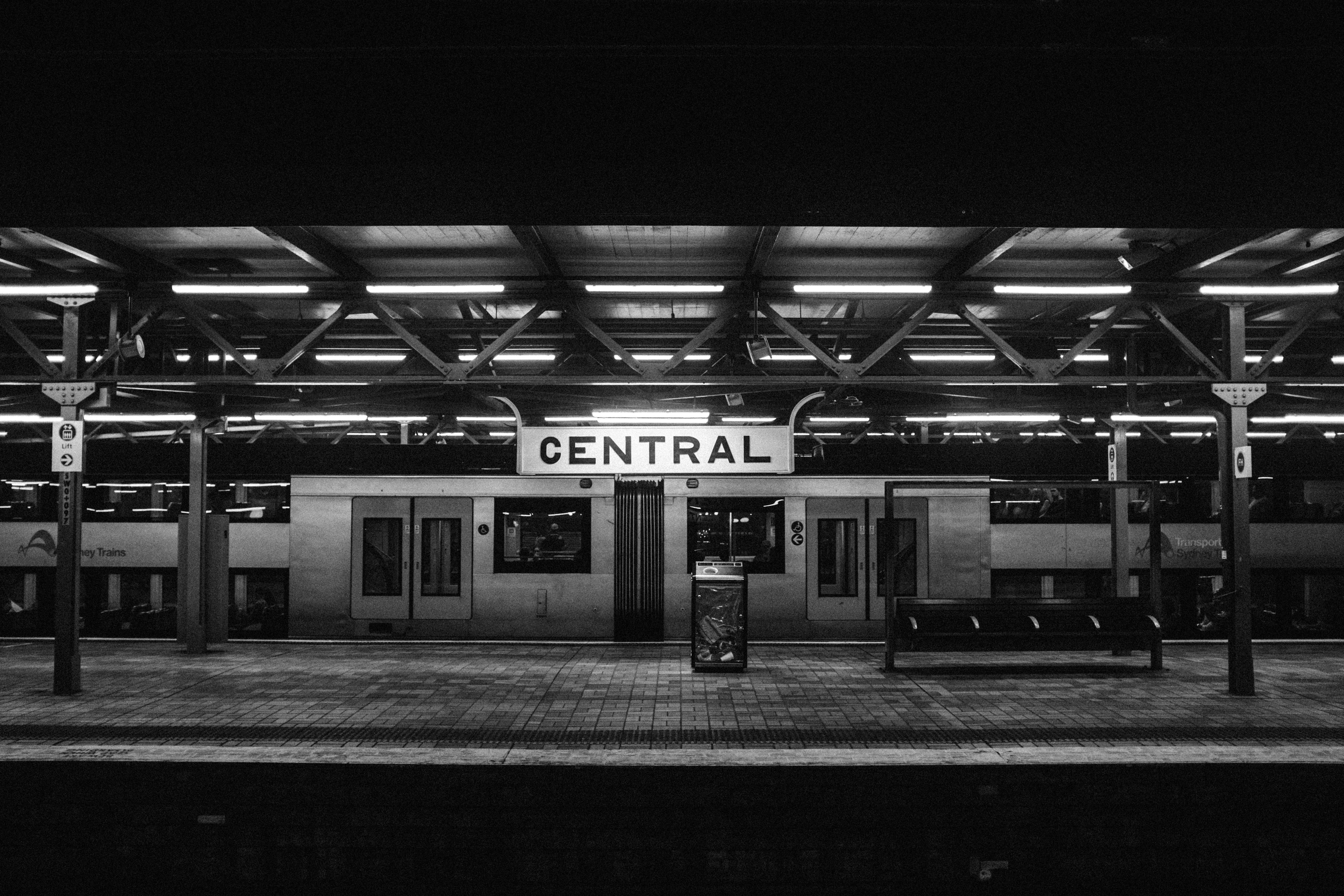 """Train station in black and white at night with the sign """"CENTRAL"""""""