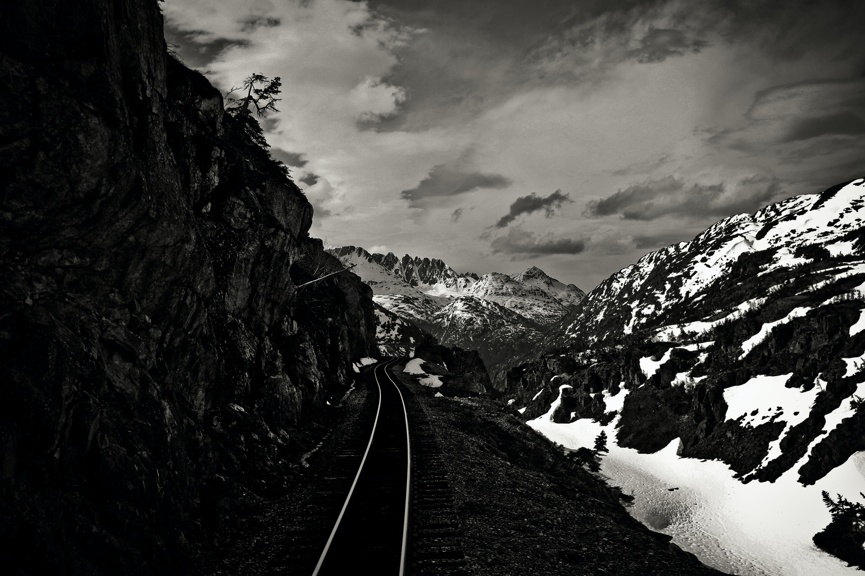 gray train rail beside snow covered mountain