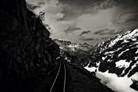 gray train rail beside snow covered mountain