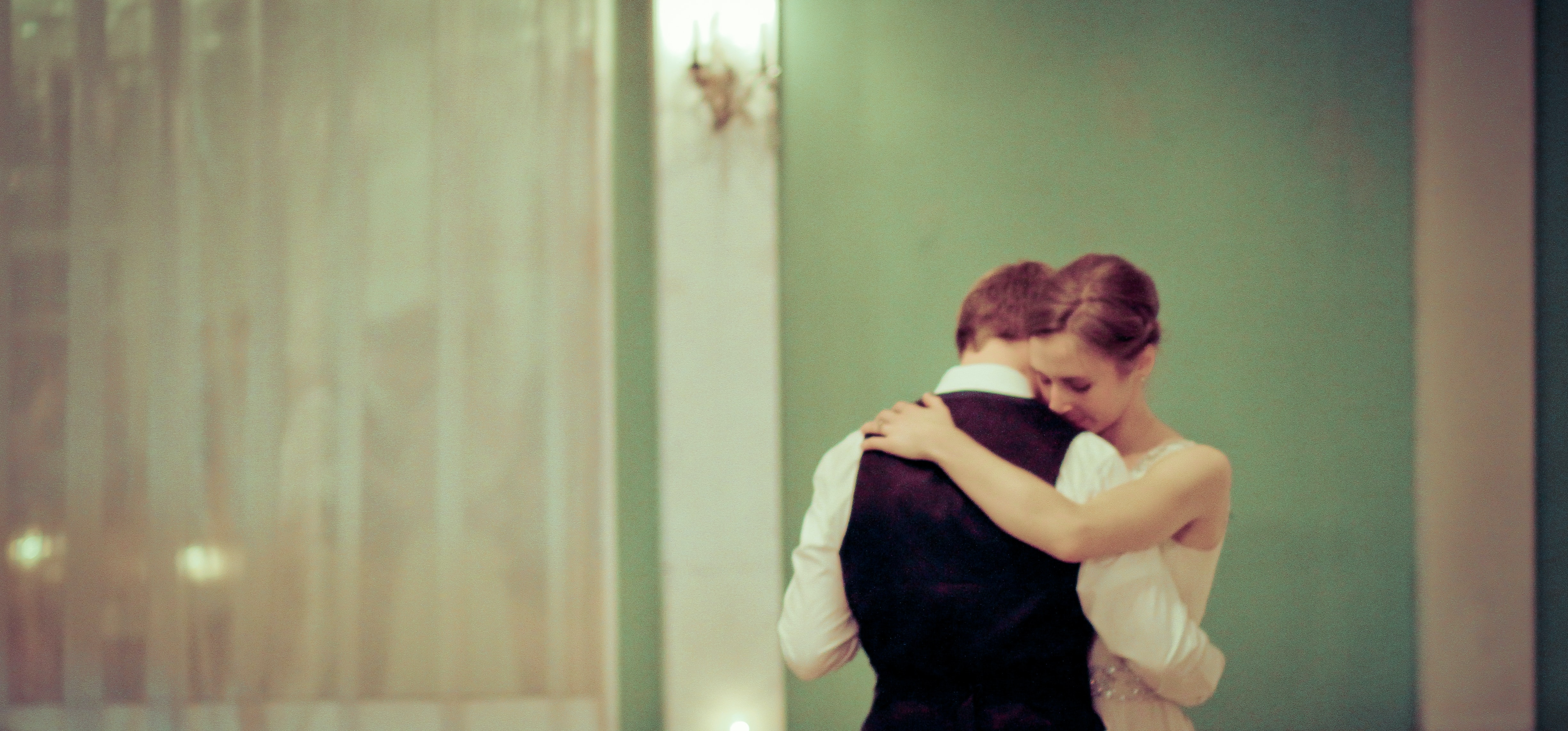 Bride and groom dance quietly together in a green-painted room