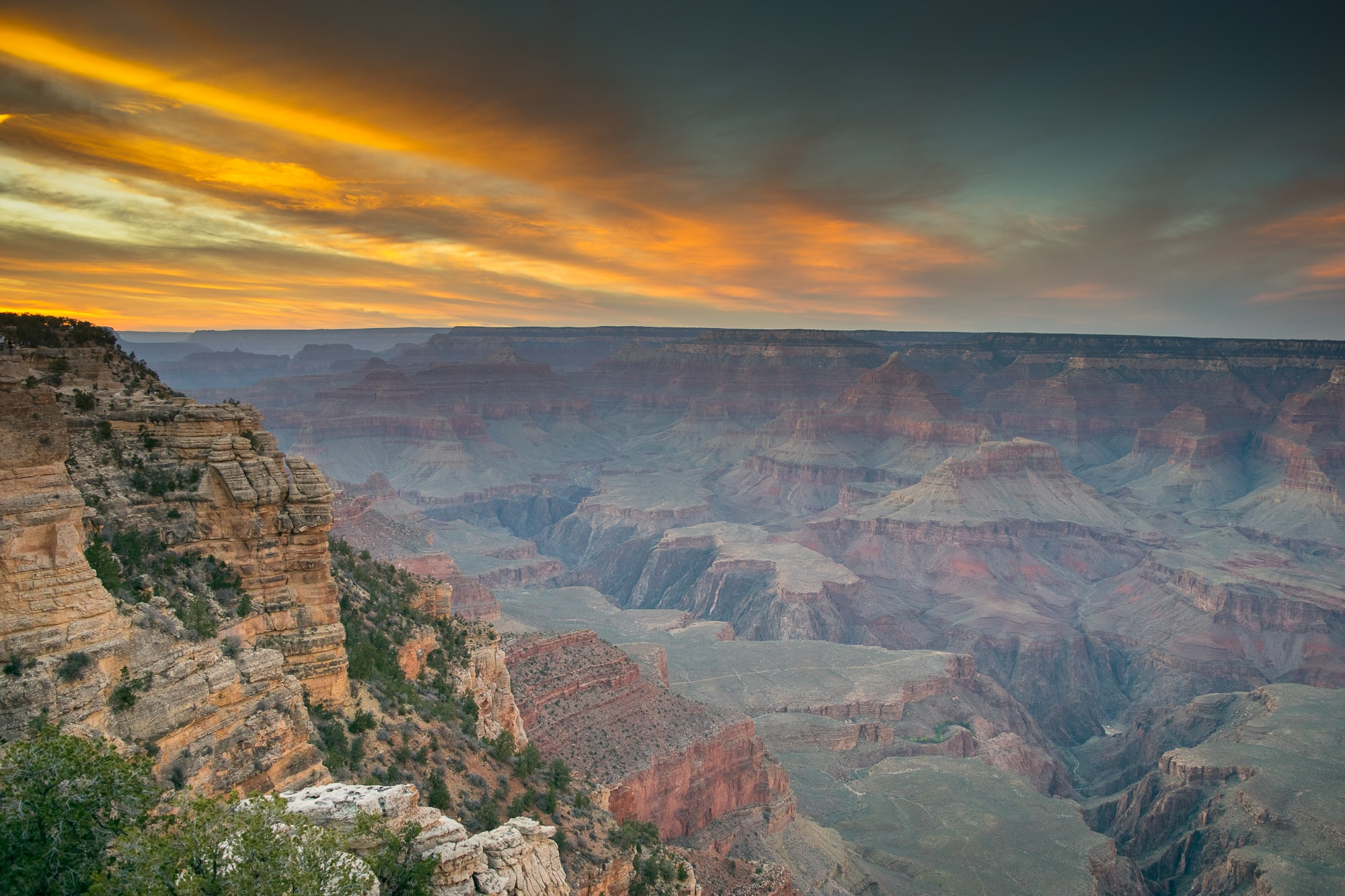 A monumental landscape with a vast canyon under the evening sky