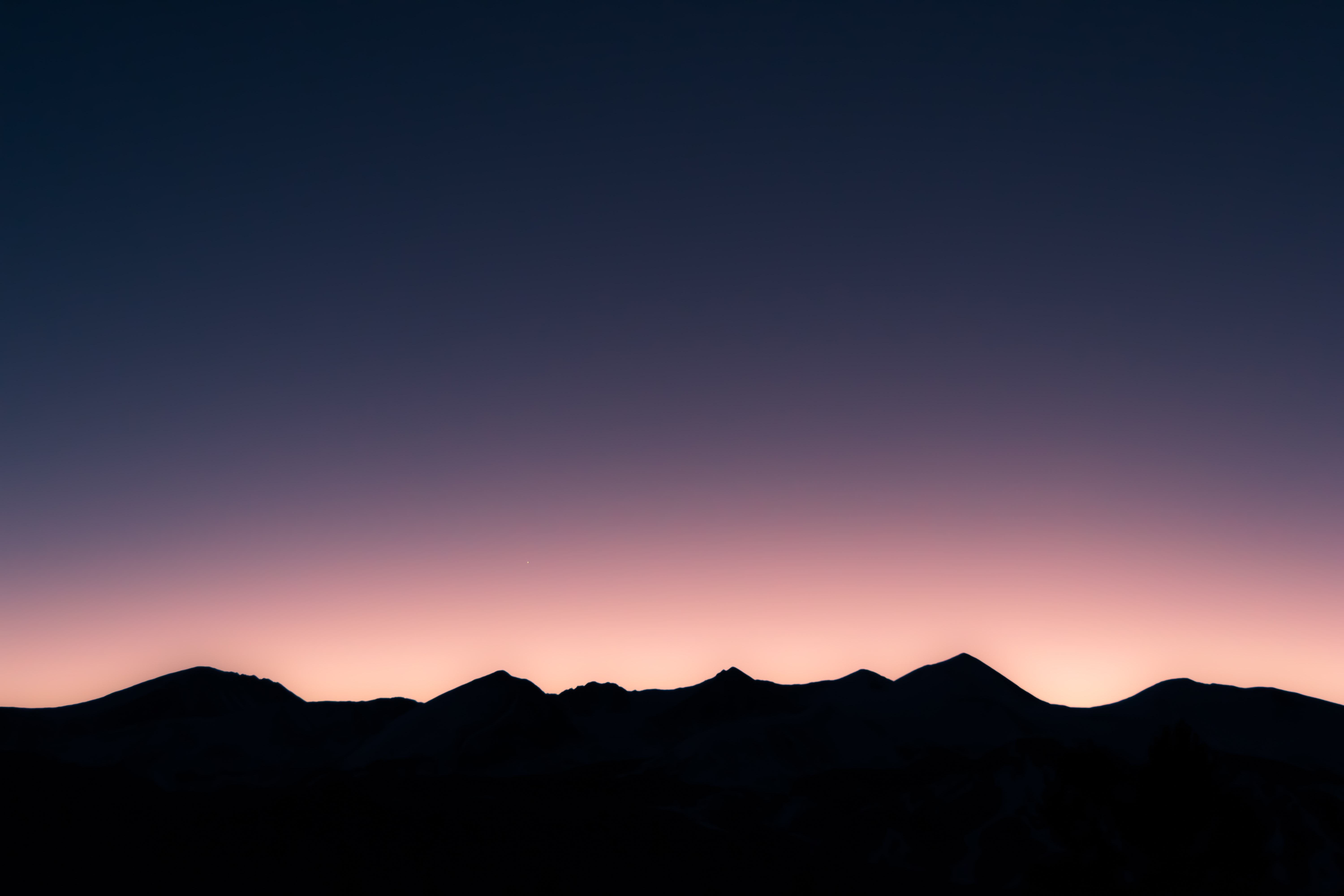 Dark silhouettes of lofty mountaintops under a purple evening sky