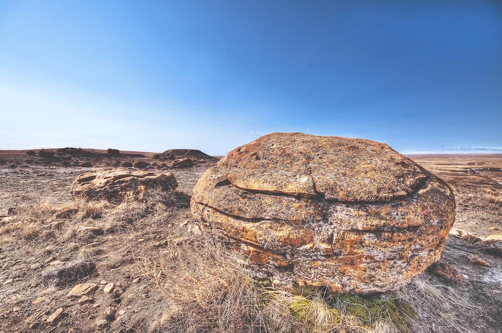 brown rock on deserted land under blue sky during daytime