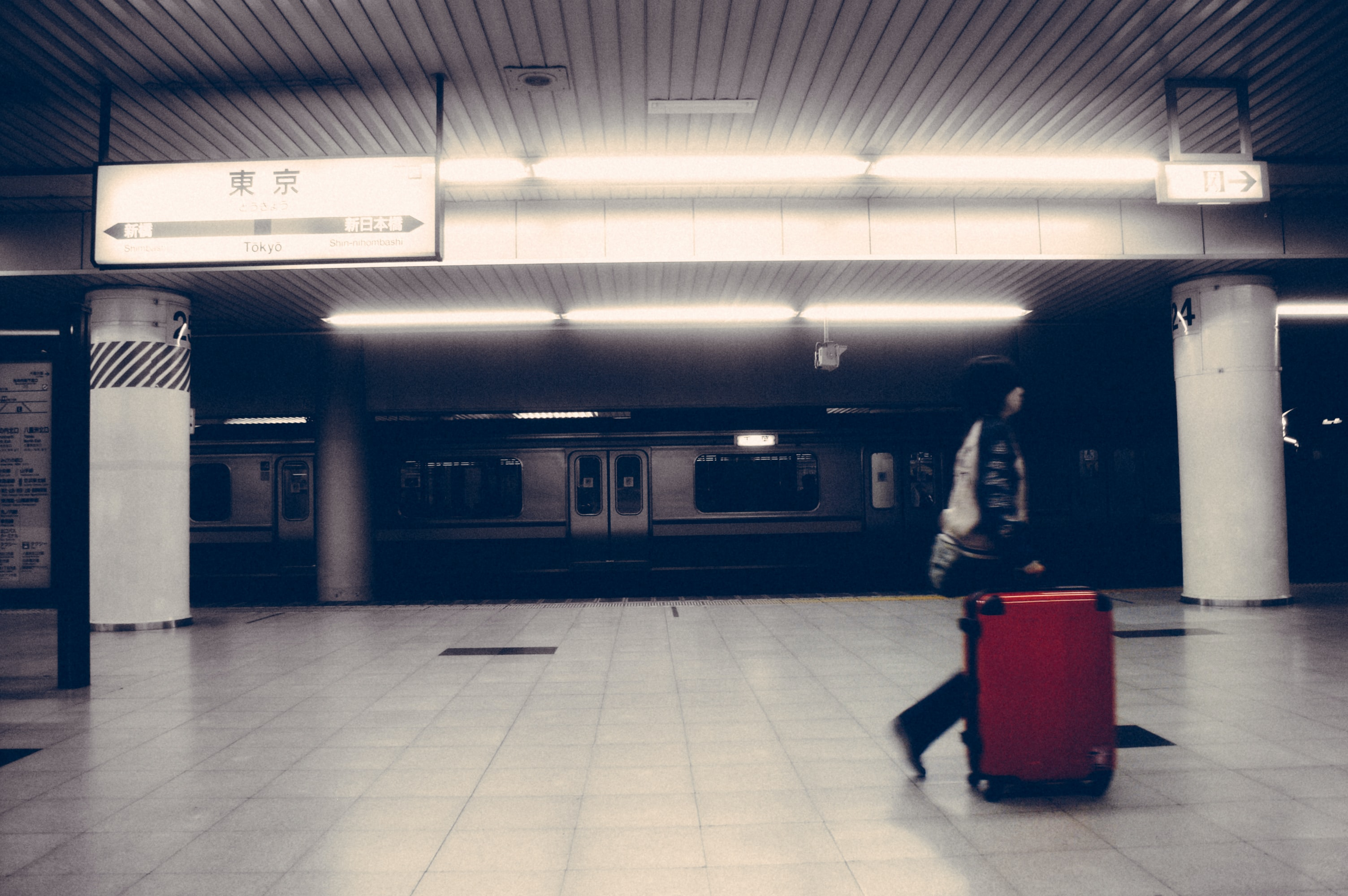 Person with red suitcase walks past a subway car in an underground station