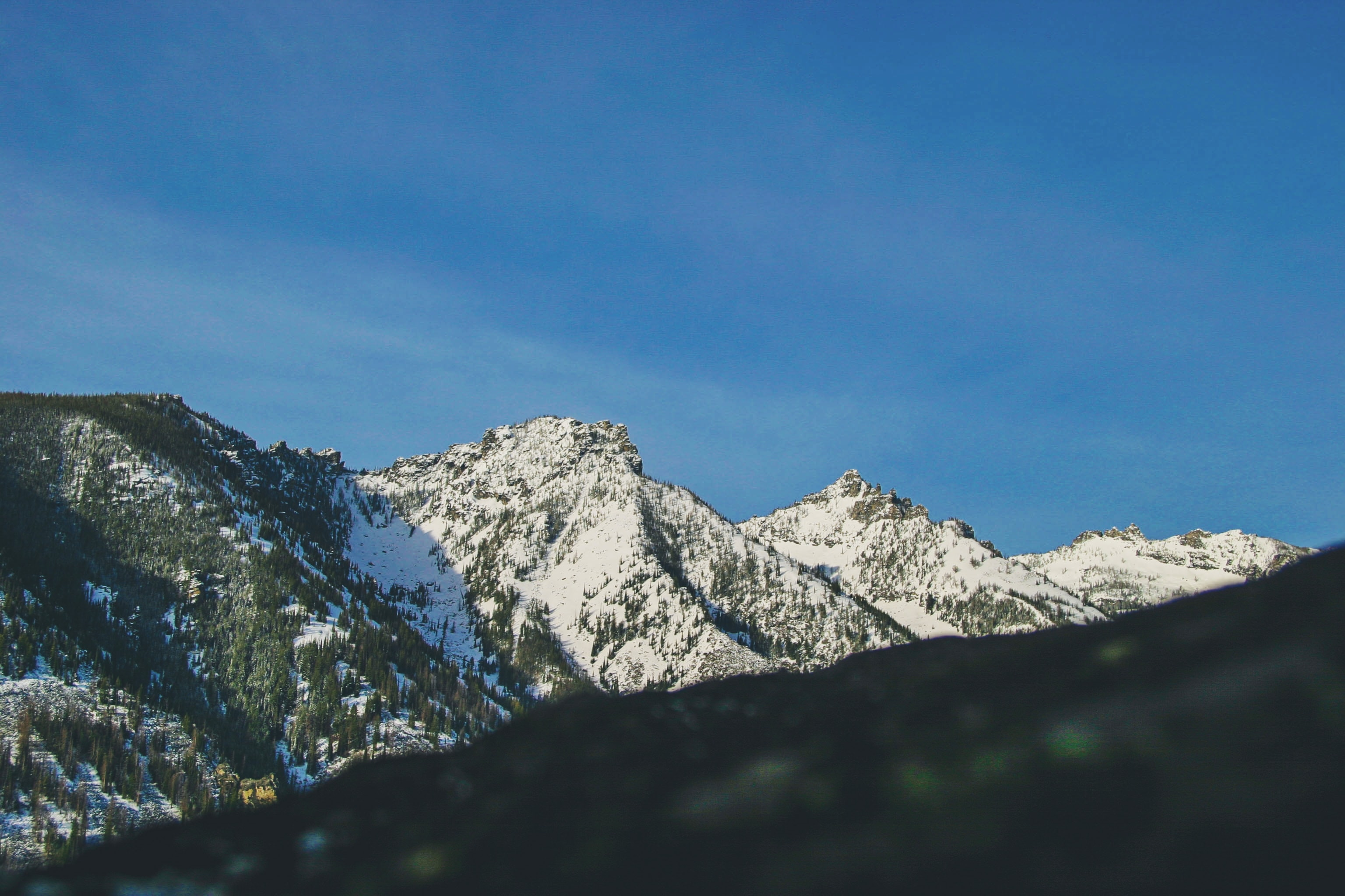 Snow-capped mountain slopes under blue sky