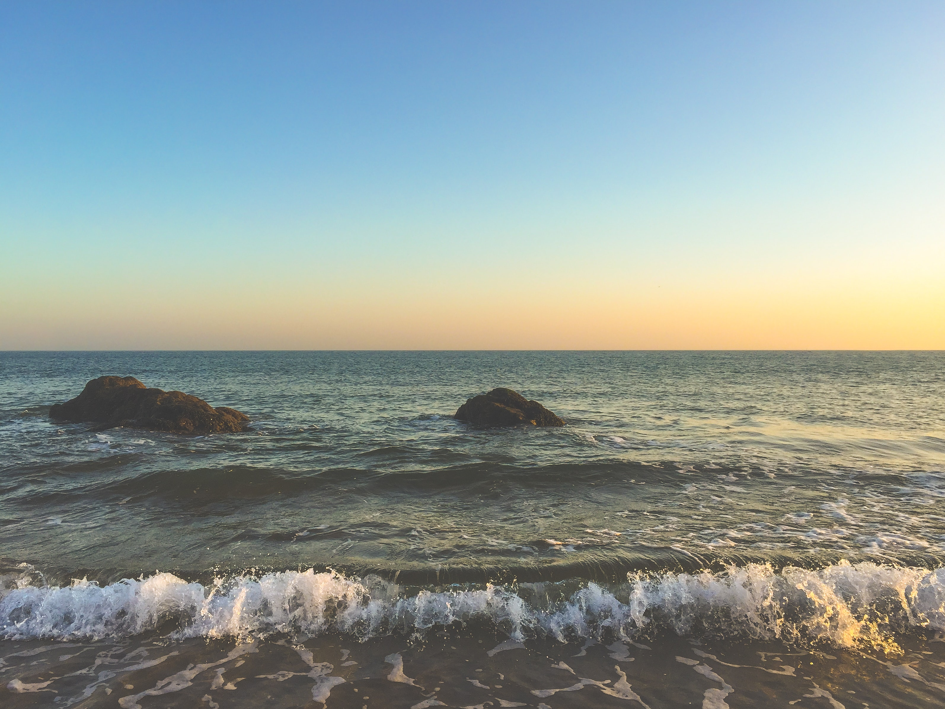 Ocean waves washing on the shore at sunset