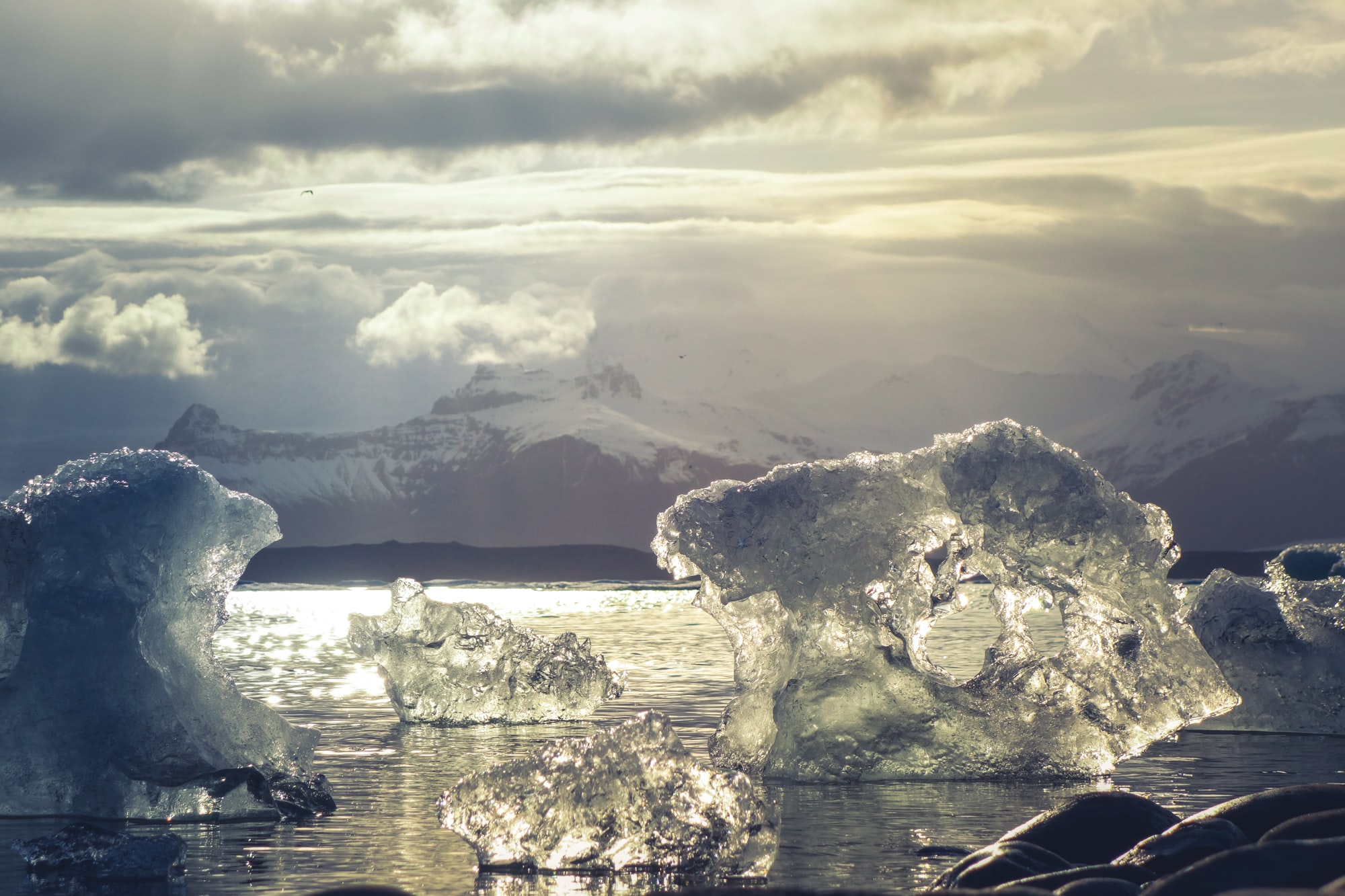 Sun gleams through clouds and reflects on icebergs in the sea