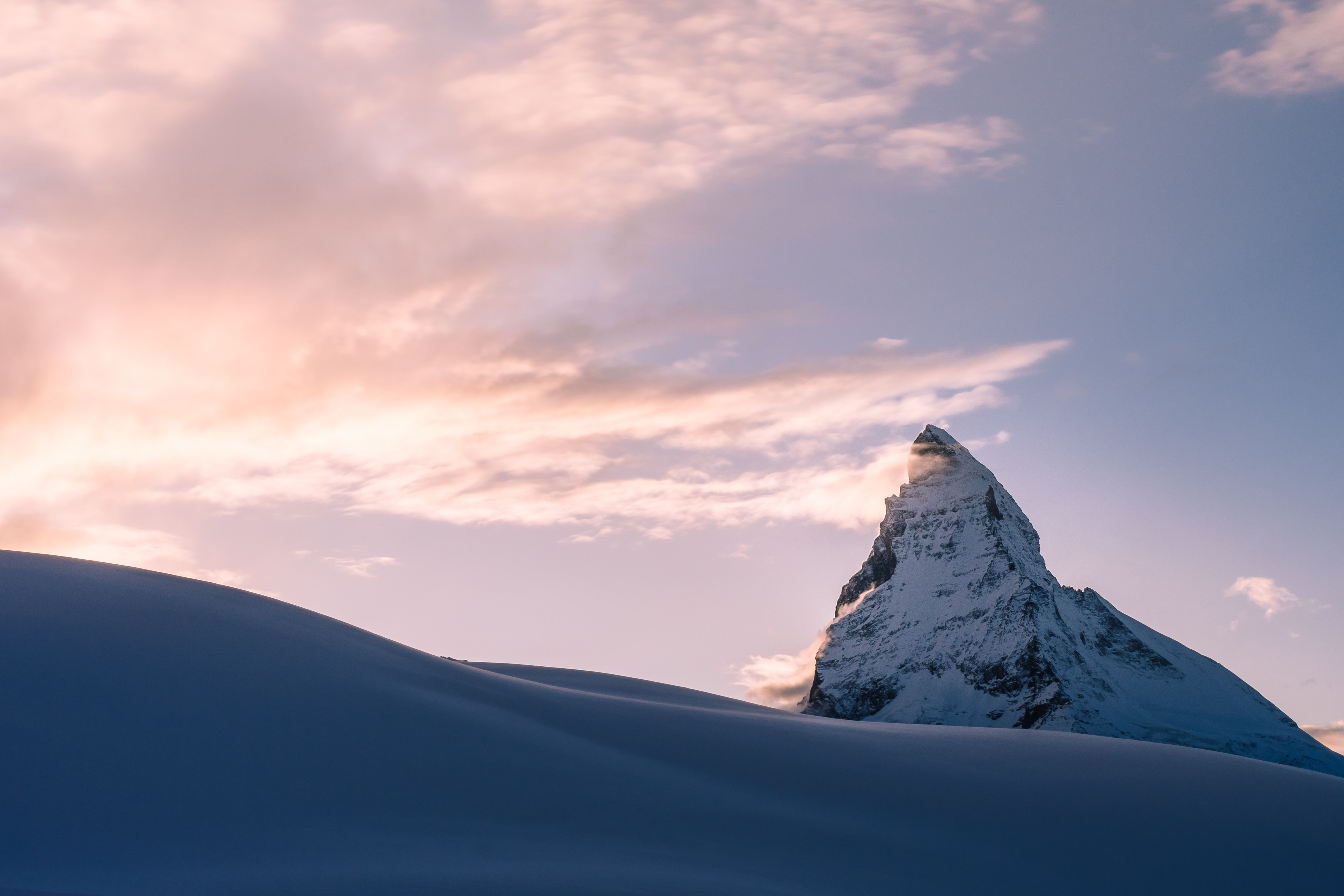 A snowy mountain peak extends towards the sky during a sunset or sunrise