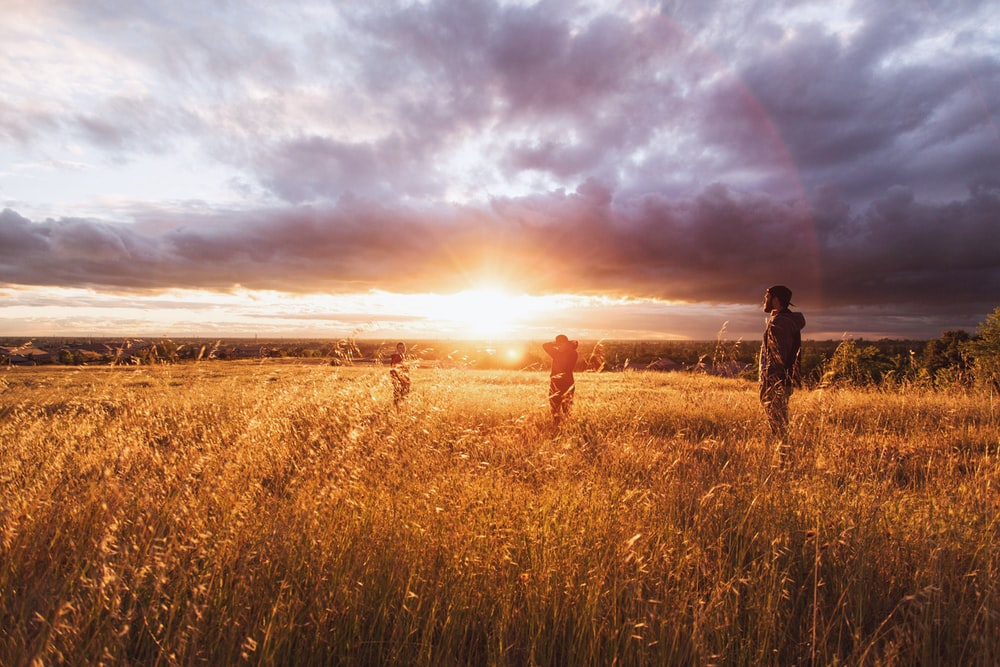 three person standing on brown grass under white clouds during sunset