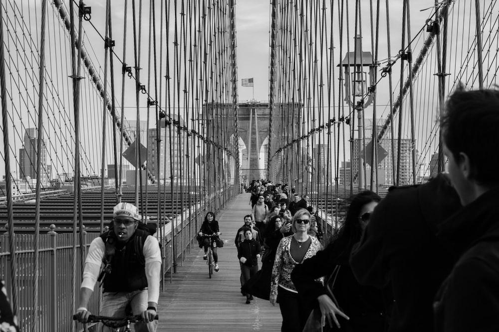 grayscale photo of people on bridge