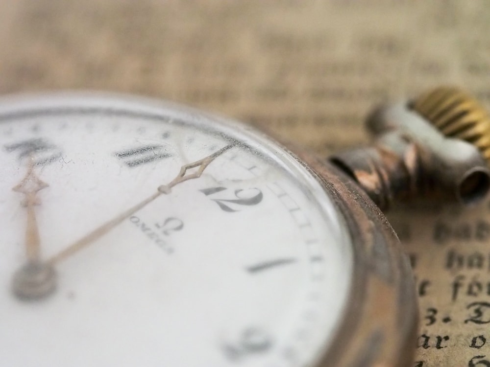 closeup photo of gold-colored pocket watch