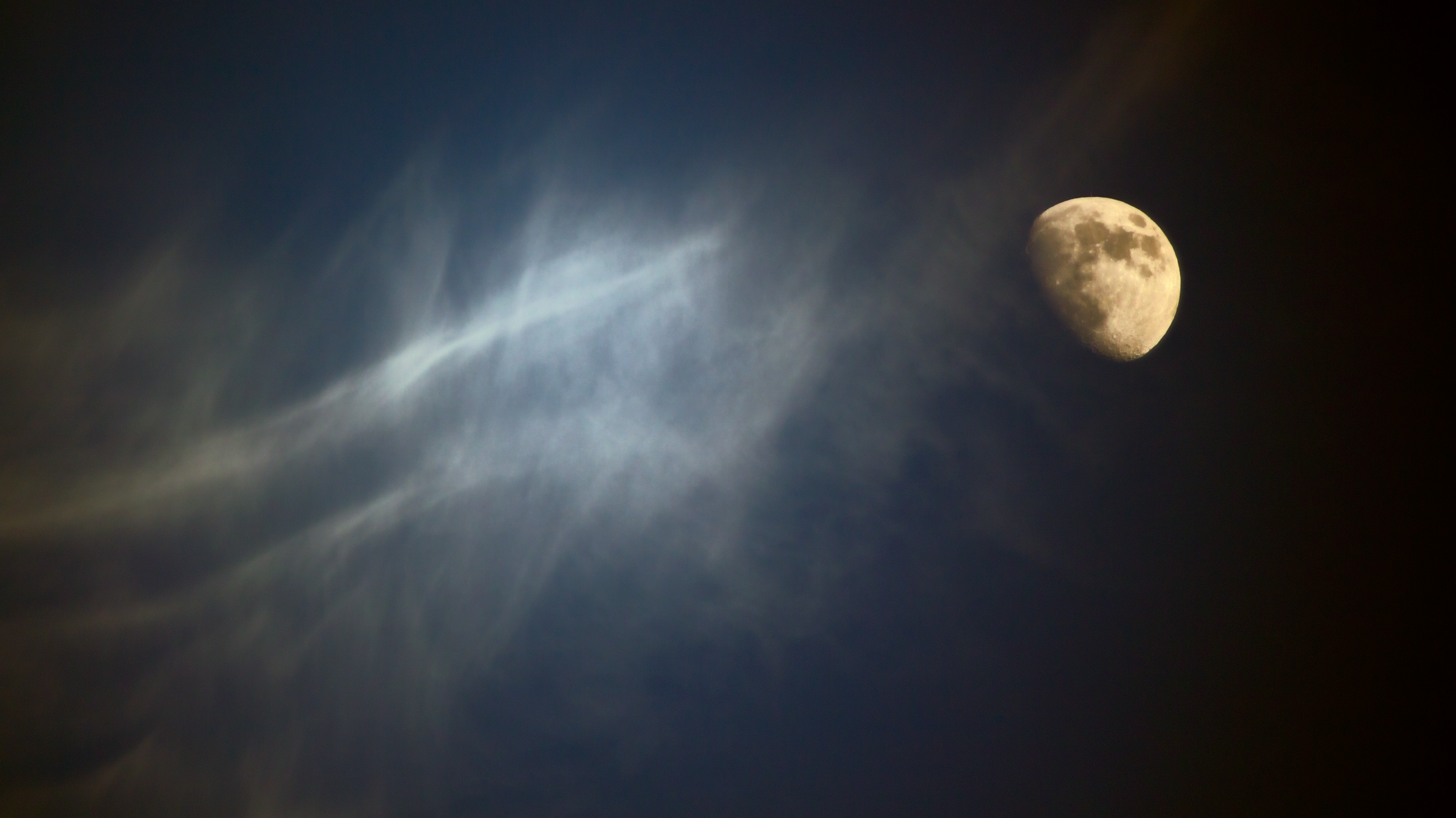 A waning moon on a cloudy night sky