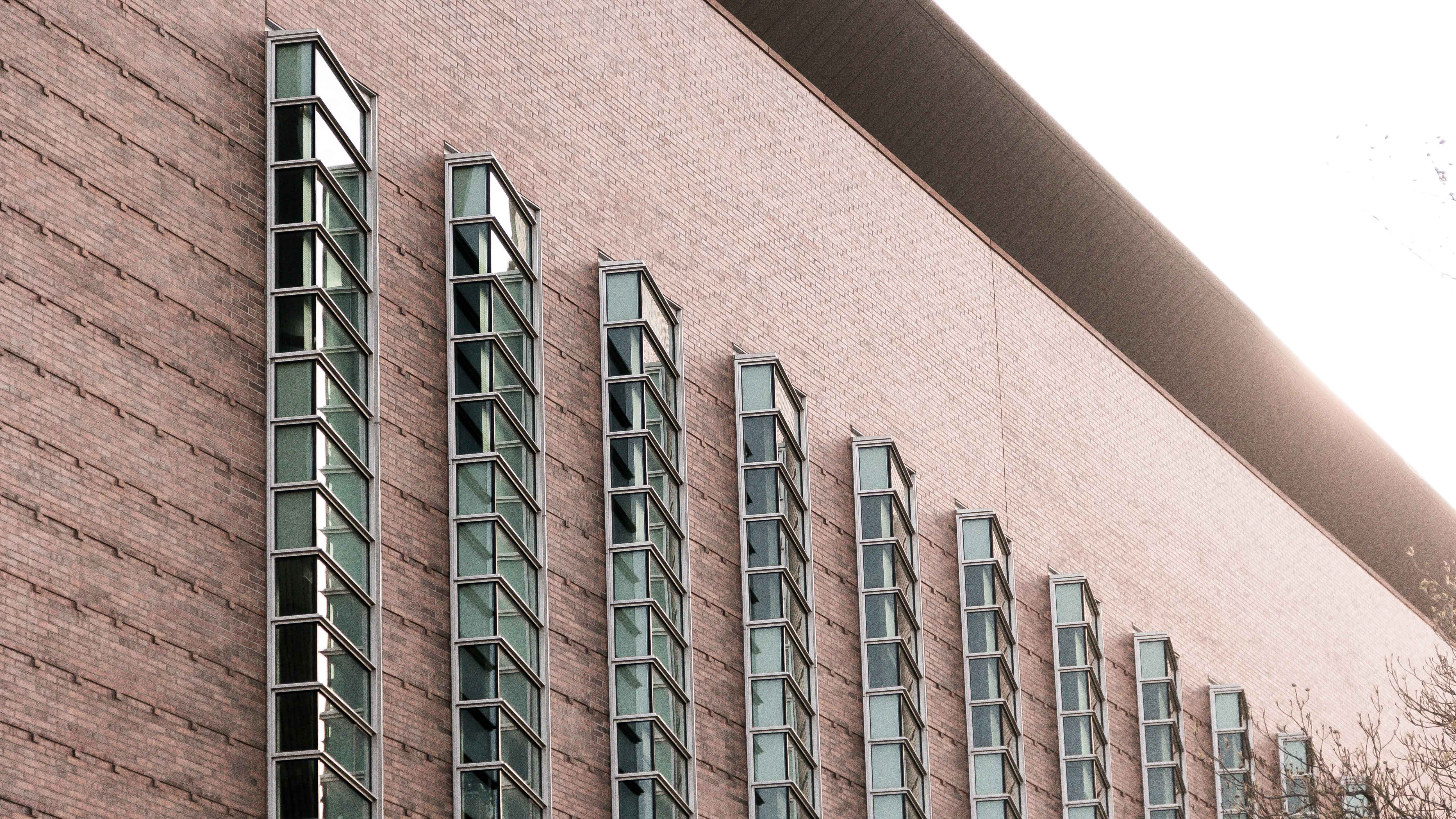 Tall barred windows on red brick building wall with clear sky