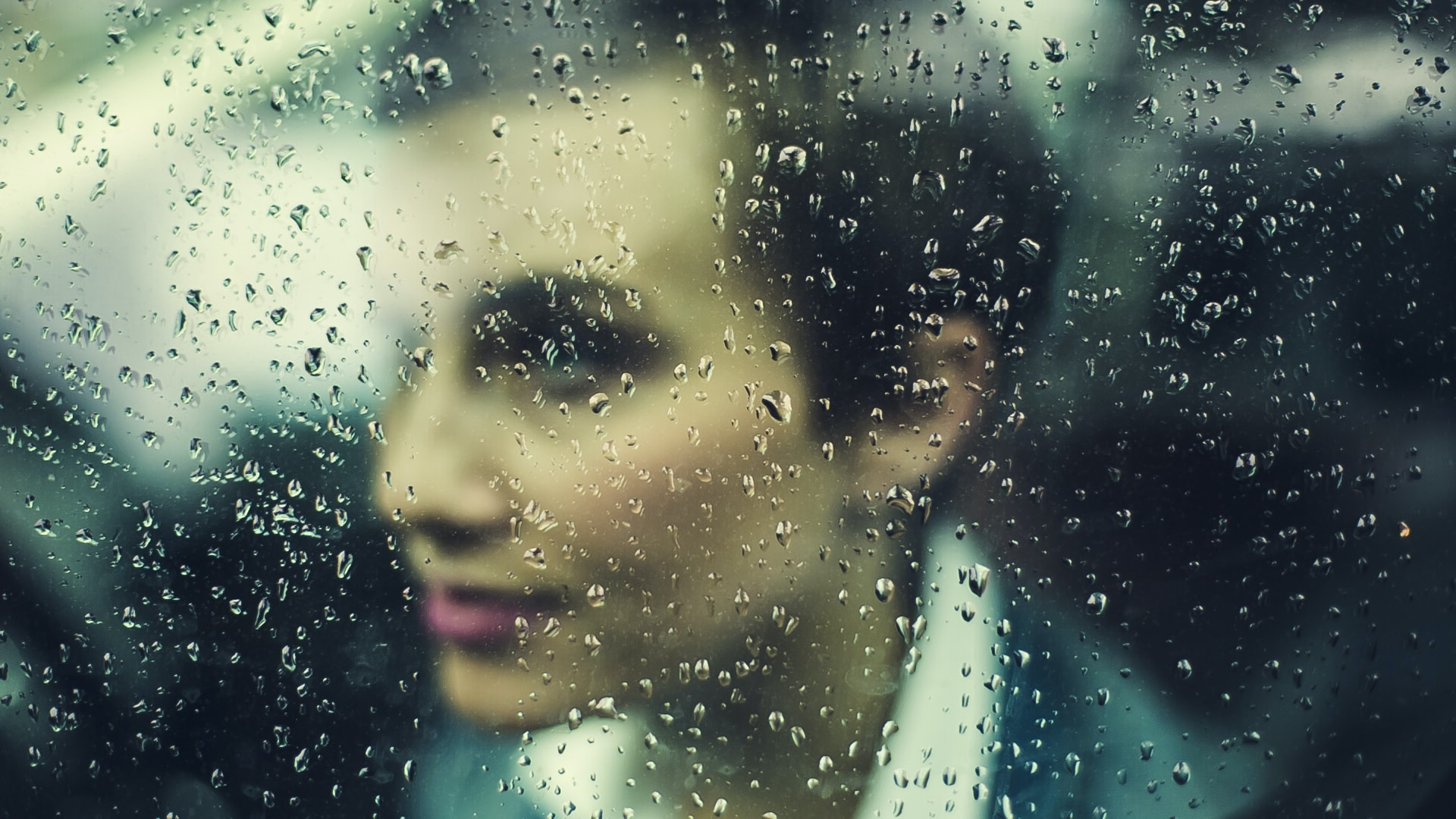 A woman's face seen through a rain-streaked window
