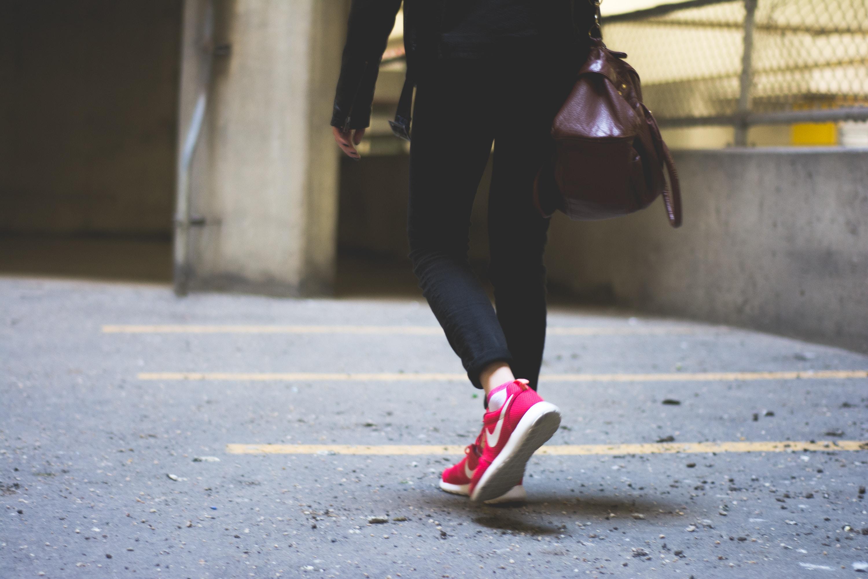 person wearing Nike running shoes walking along the path