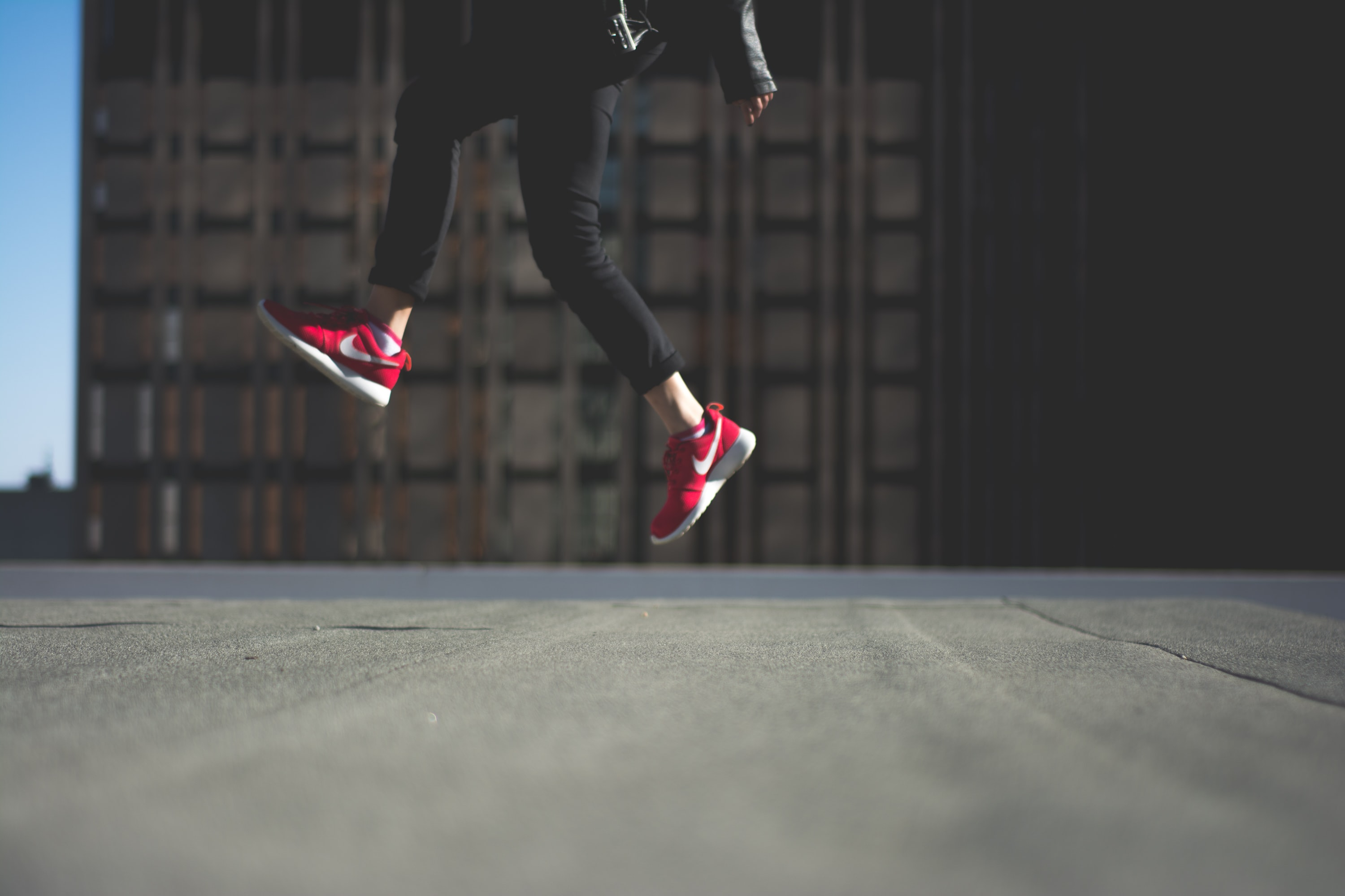 person wearing pair of red Nike shoes