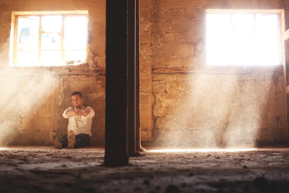 man sitting beside concrete wall