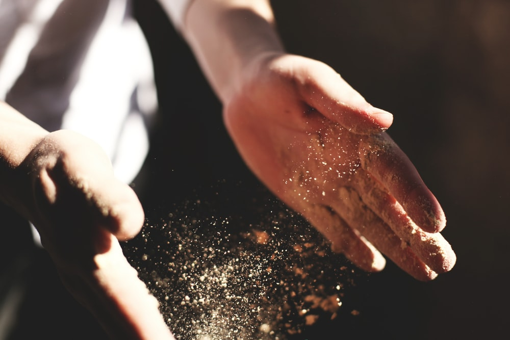 person's hand with dust during daytime